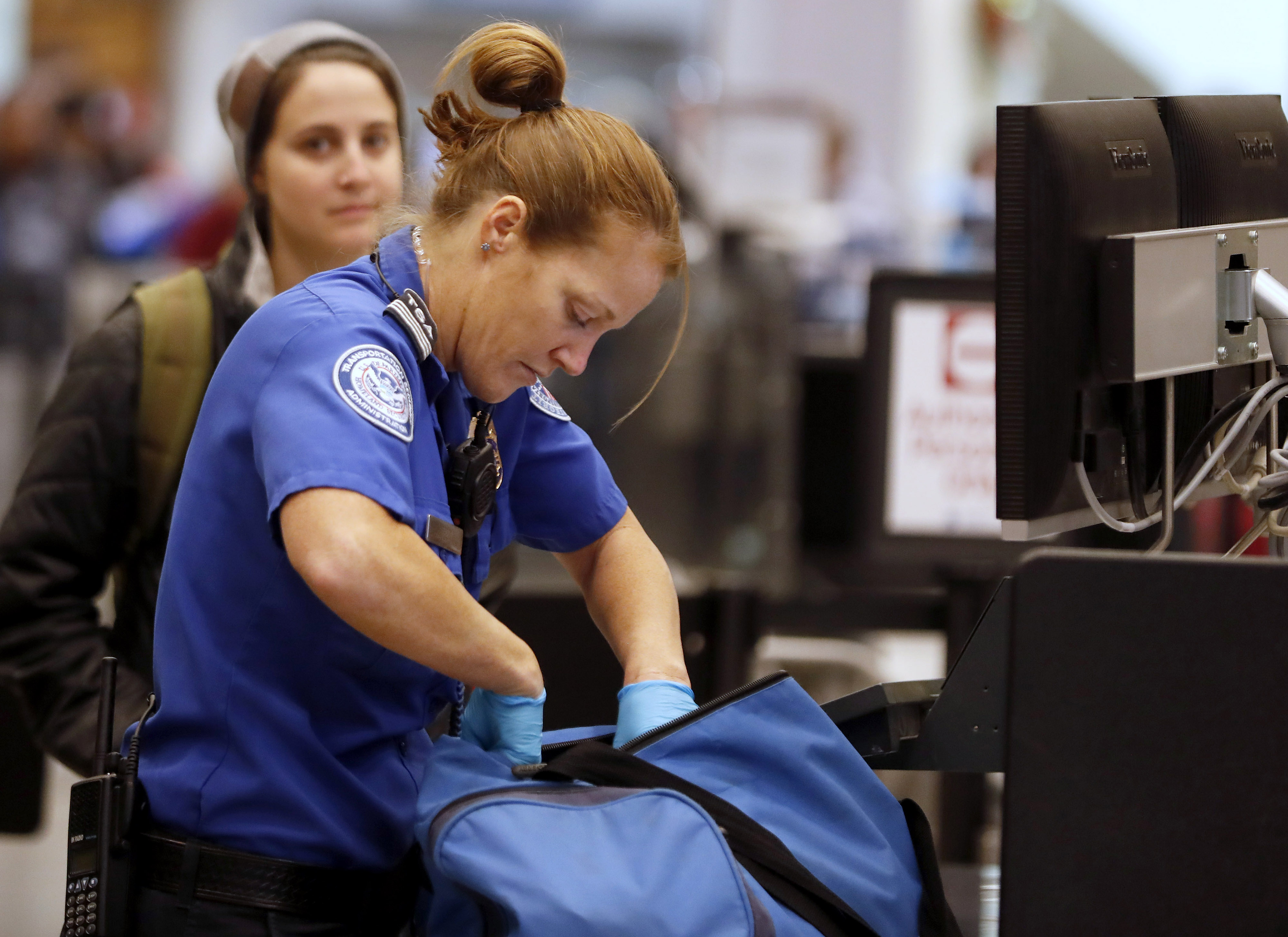 A Transportation Security Administration (TSA) officer checks a traveler's bag at a screening location at Salt Lake City International Airport (SLC) in Salt Lake City, Utah, U.S., on Friday, Dec. 23, 2016. Bloomberg—Bloomberg via Getty Images