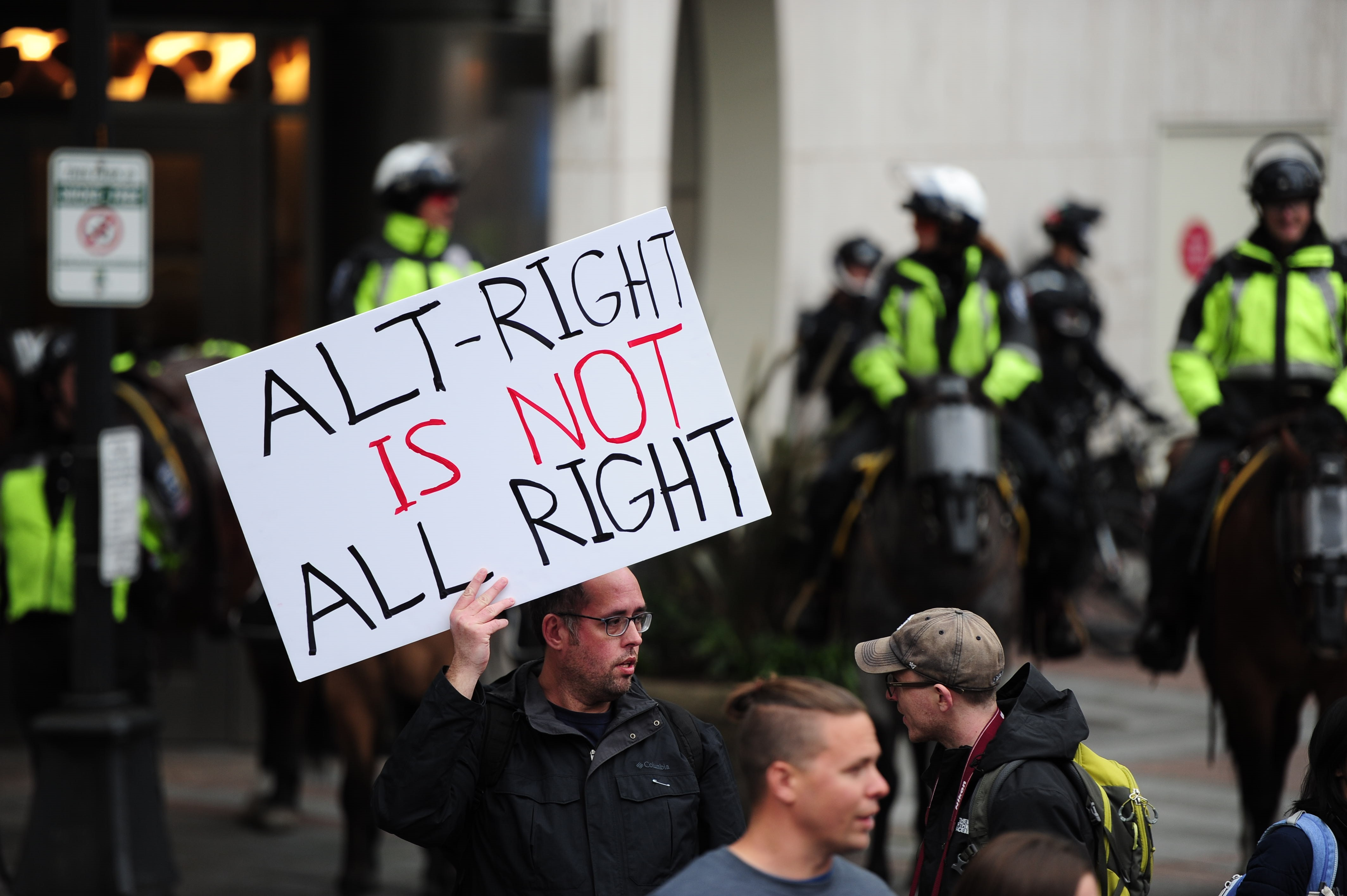 A man holds a sign against the alt-right as Trump supporters gather for a  Stand Against Communism  rally at Westlake Park in Seattle, Wash., on May 01 2017.