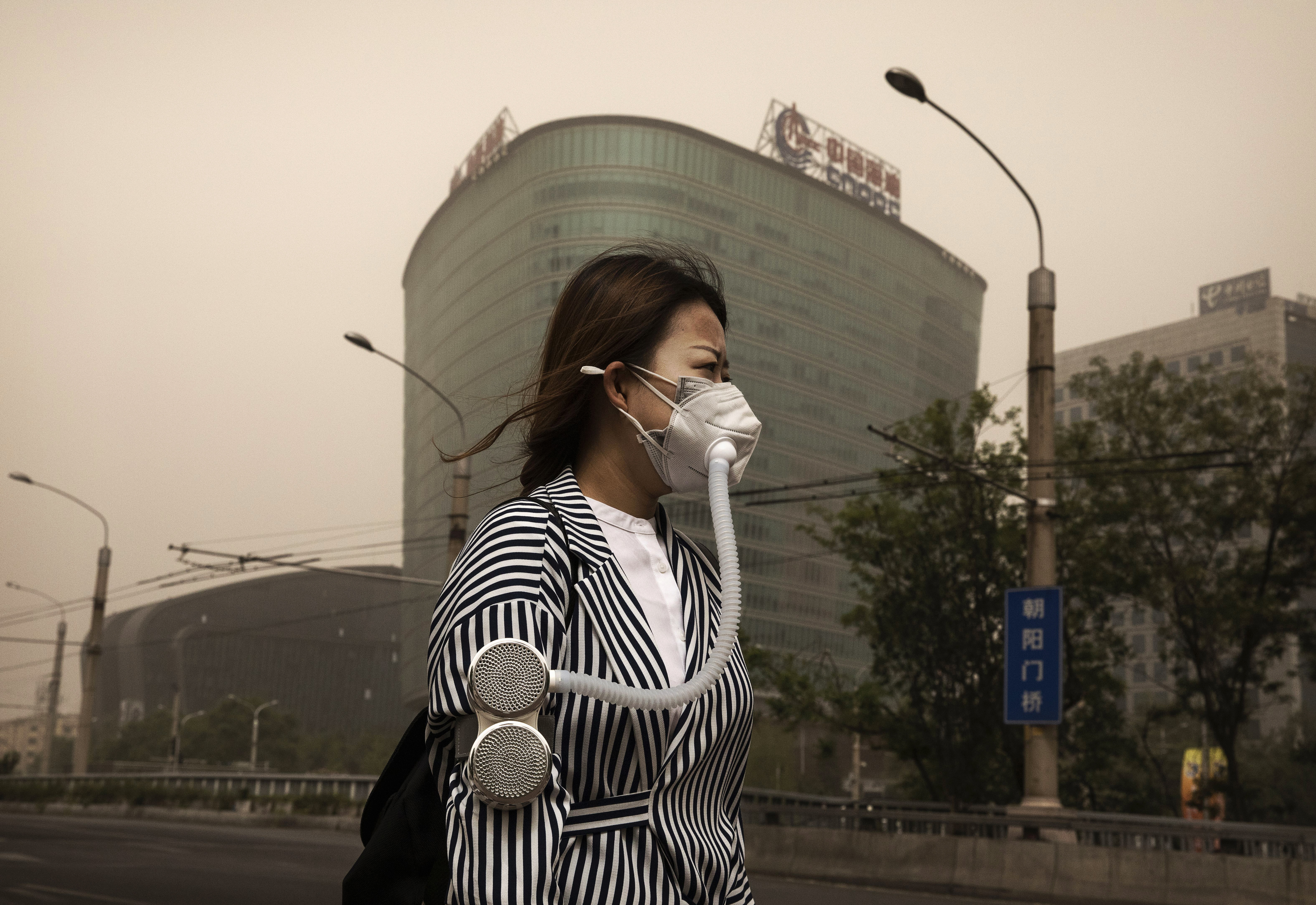 A Chinese woman wears a mask to protect from particles blown in during a sandstorm as she walks in the street on May 4, 2017 in Beijing, China.