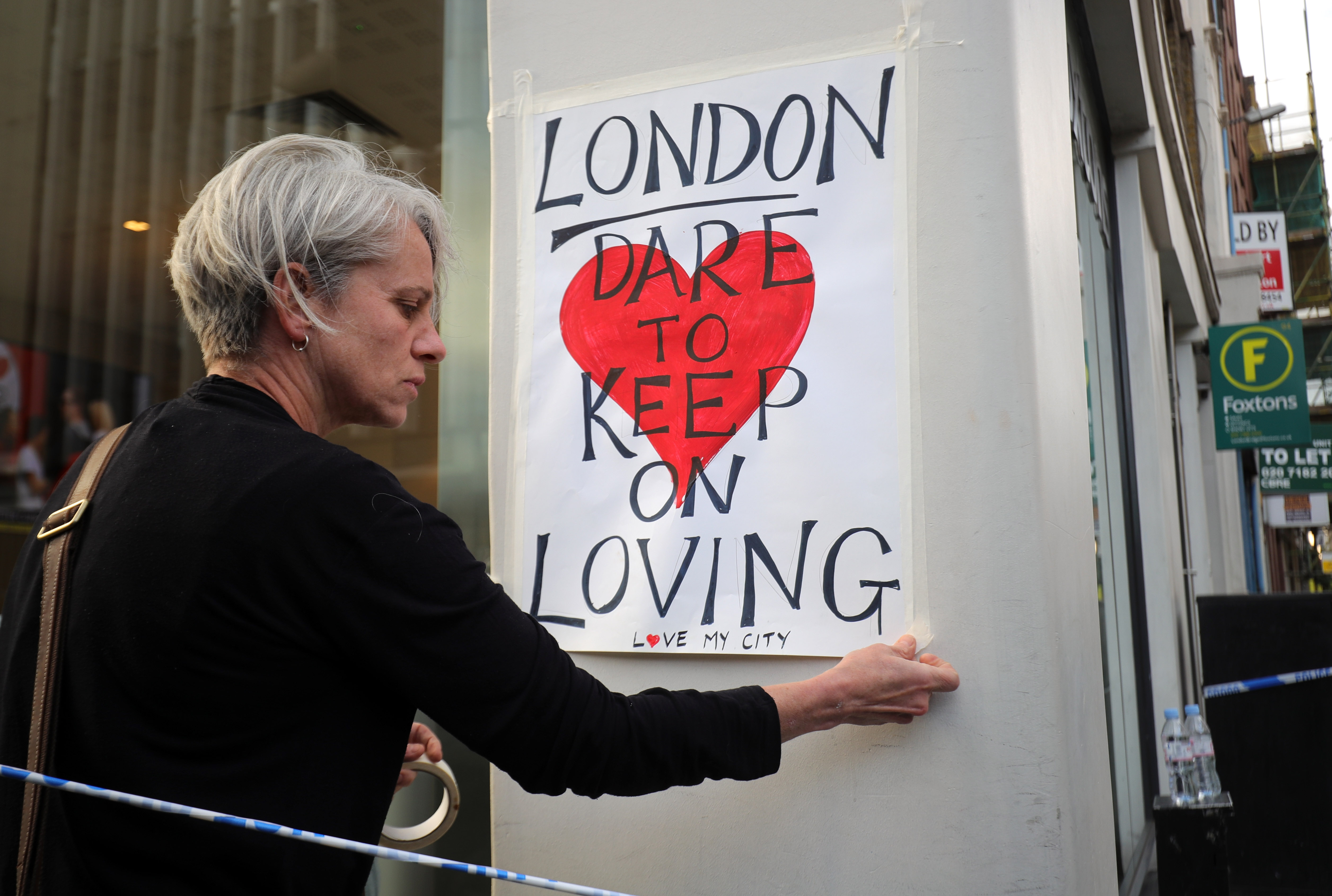 A woman places posters around the city near the scene of Saturday night's terrorist attack on June 4, 2017 in London, England.