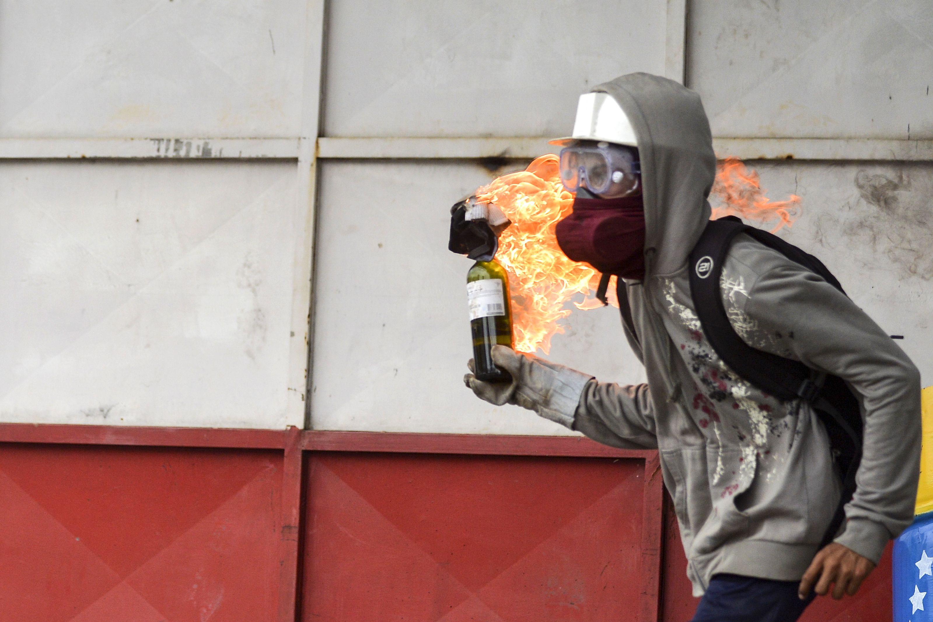 An opposition activist hurls a Molotov cocktail at riot police during clashes in Caracas on June 7, 2017.