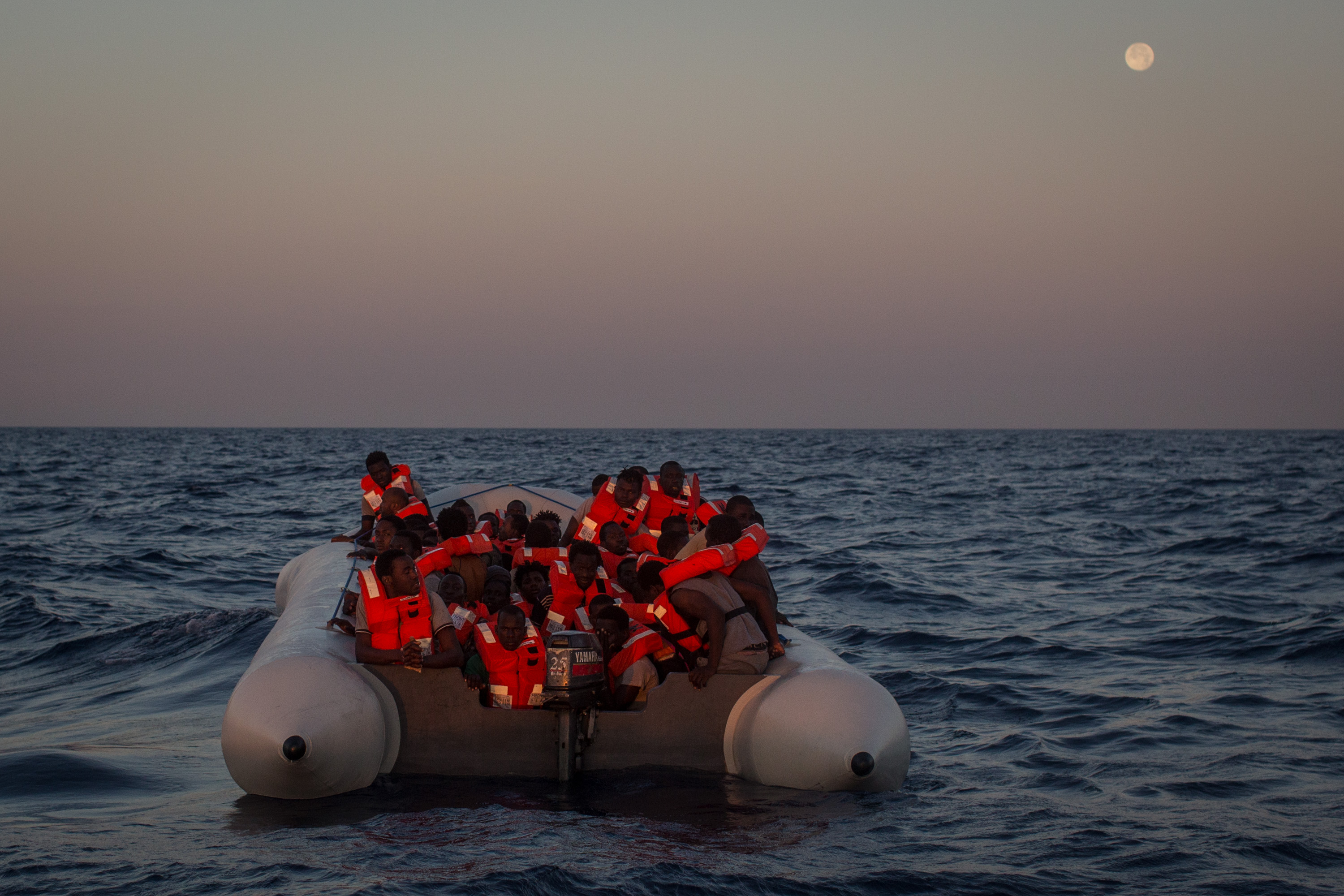 Refugees and migrants wait in a small rubber boat to be rescued by crew members from the Migrant Offshore Aid Station (MOAS) Phoenix vessel on June 10, 2017 off Lampedusa, Italy.