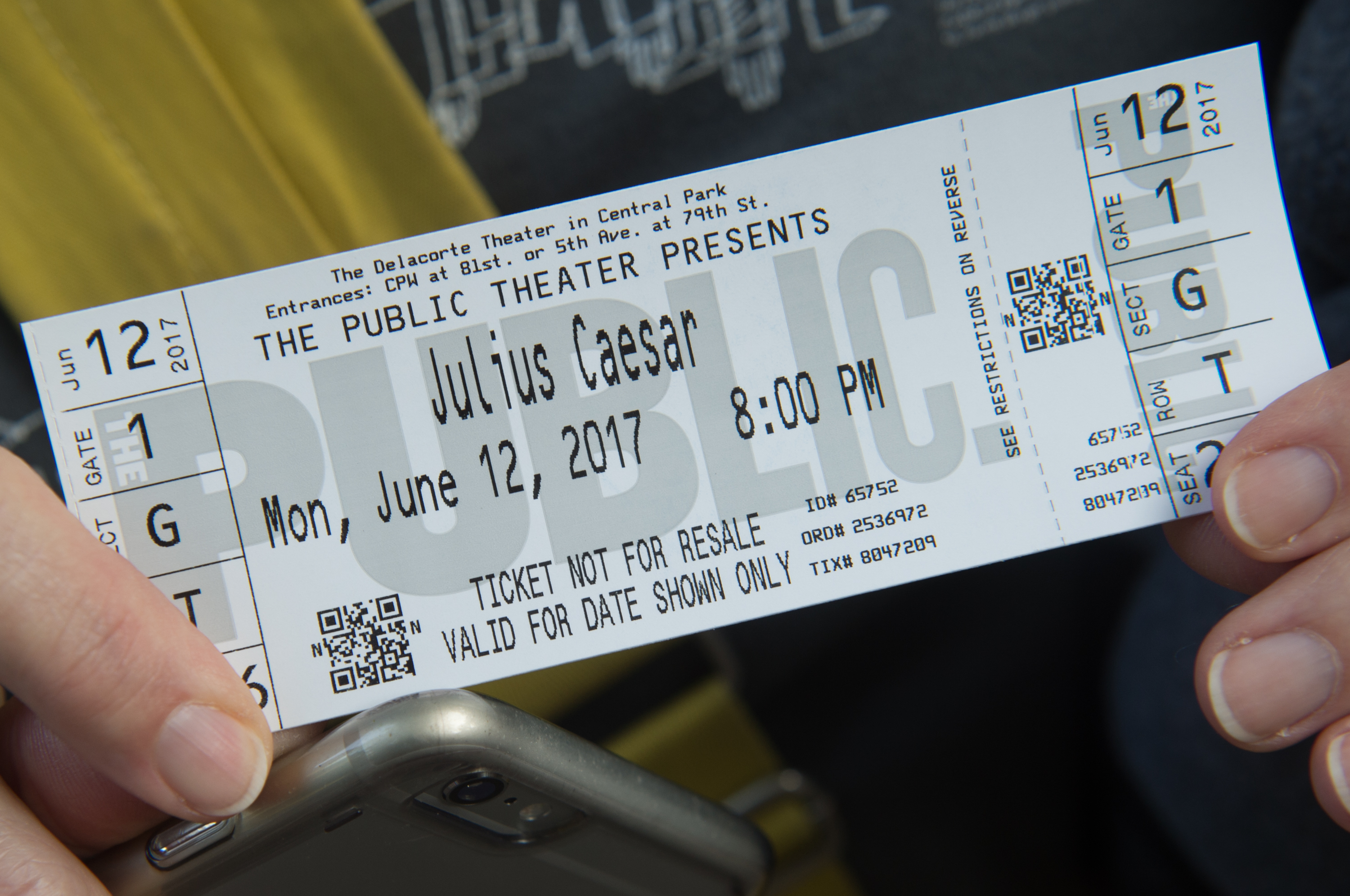 A woman holds her ticket to opening night of Shakespeare in the Park's production of Julius Caesar at Central Park's Delacorte Theater on June 12, 2017 in New York.