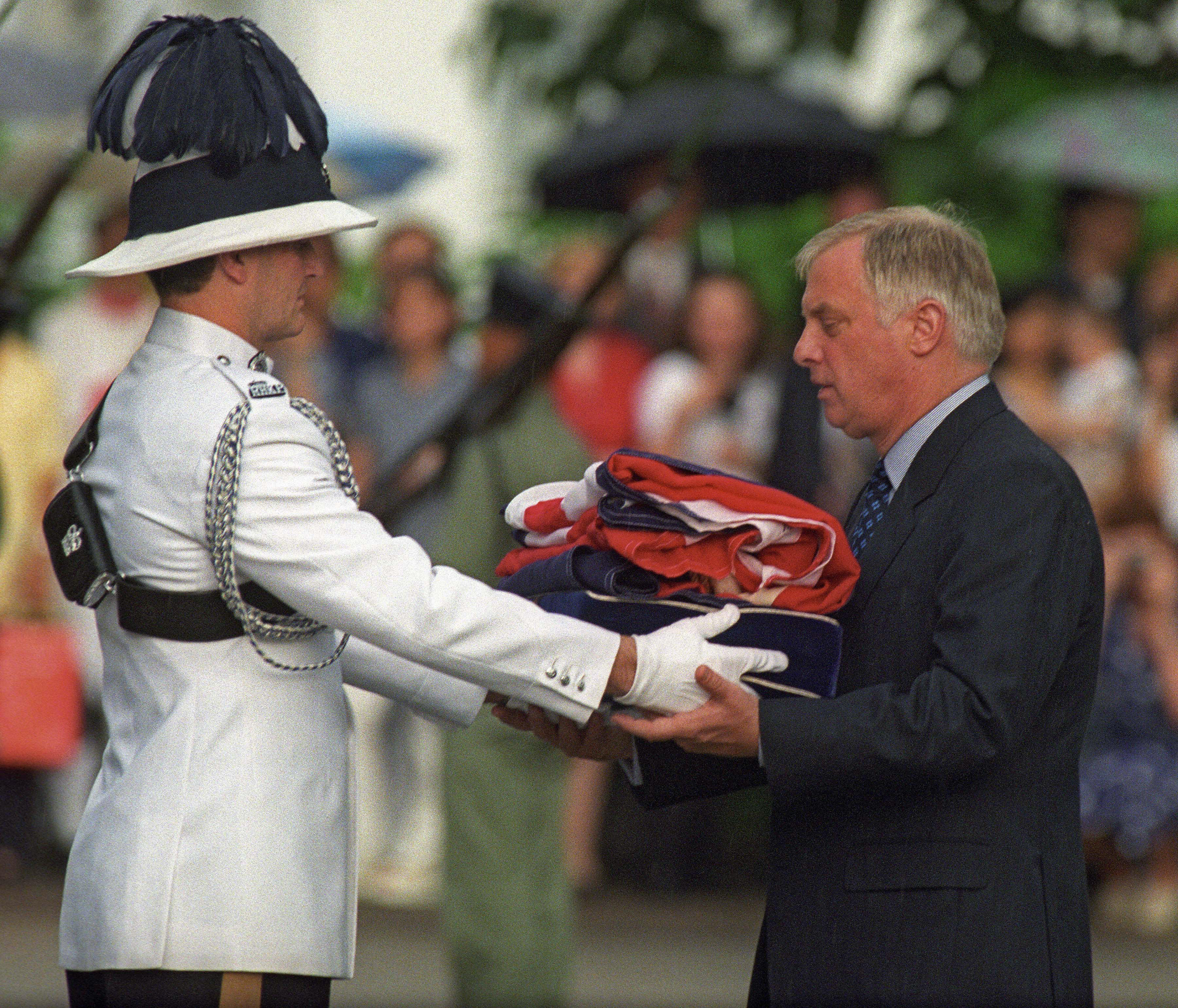 Chris Patten (R), the 28th and last governor of colonial Hong Kong, receives the Union Jack flag after is was lowered for the last time at Government House - the governor's official residence - during a farewell ceremony in Hong Kong, 30 June 1997, just hours prior to the end of some 156 years of British colonial rule as the territory returns to Chinese control.