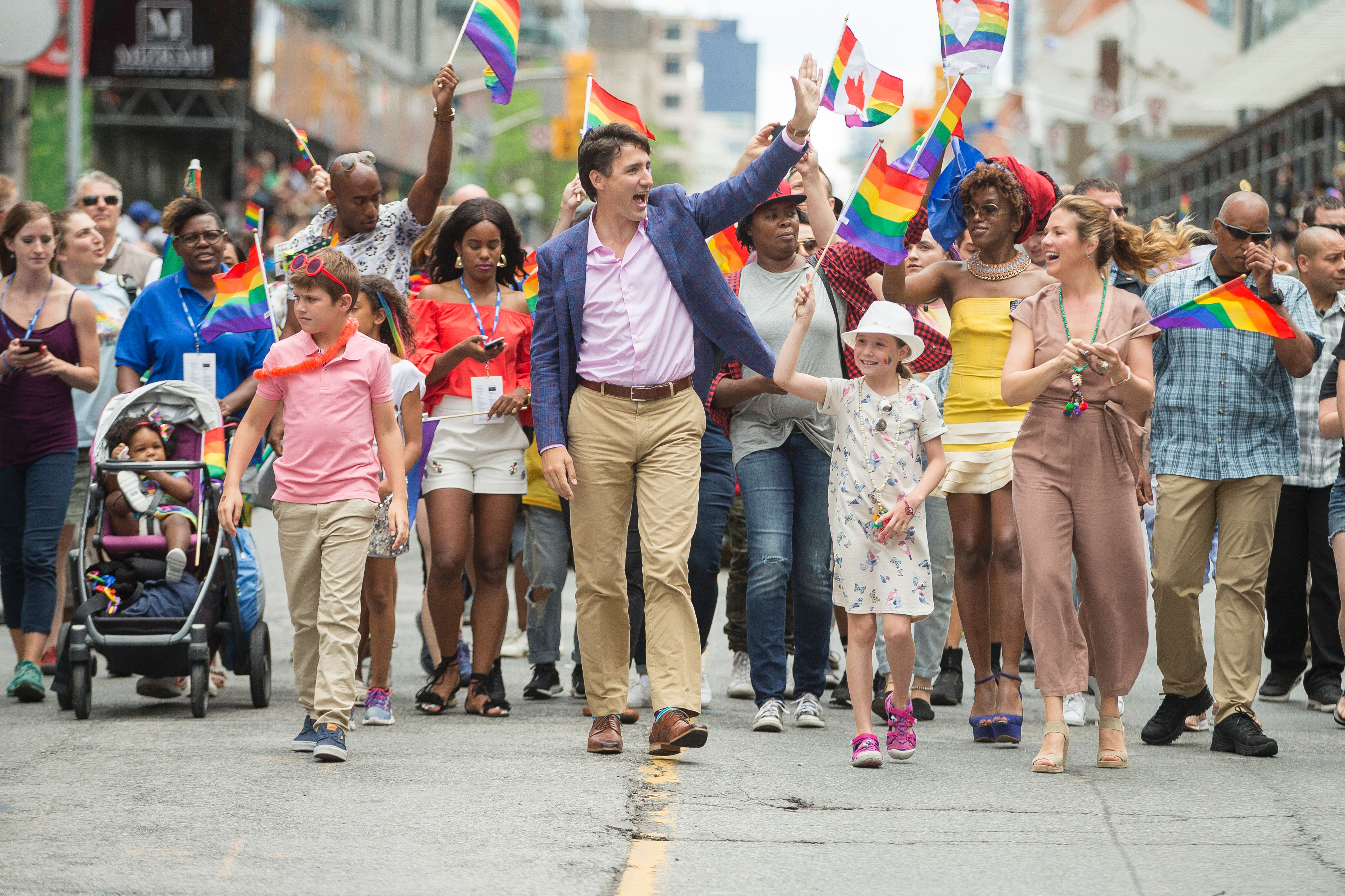 Prime Minister Justin Trudeau waves to the crowd as he, his wife Sophie Gregoire Trudeau and their children Xavier and Ella-Grace march in the Pride Parade in Toronto, June 25, 2017. / AFP PHOTO / GEOFF ROBINS        (Photo credit should read GEOFF ROBINS/AFP/Getty Images)