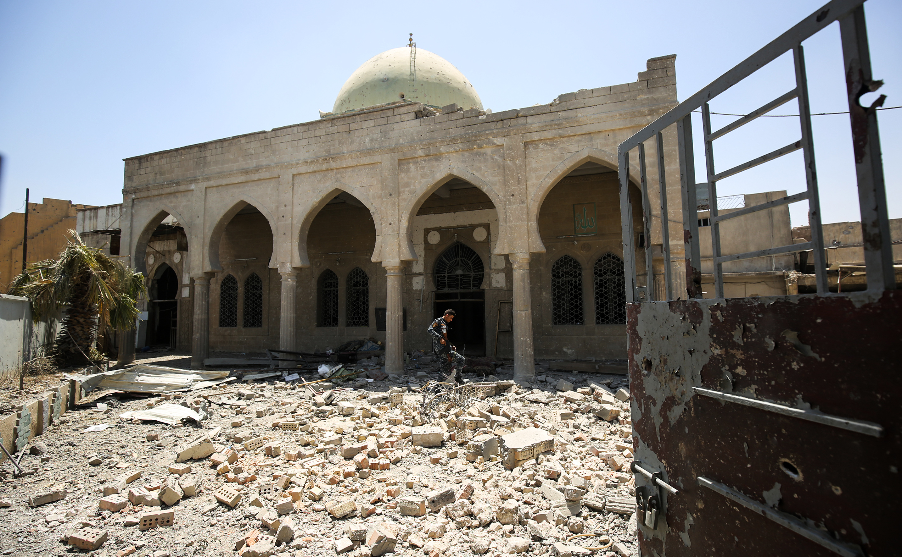 A member of the Iraqi federal police walks through the rubble in the grounds outside the damaged historic 19th century Ziwani mosque in the Old City of Mosul on June 28, 2017, as Iraqi forces inspect damage the building sustained during the offensive to retake the last remaining district from Islamic State (IS) group fighters.
