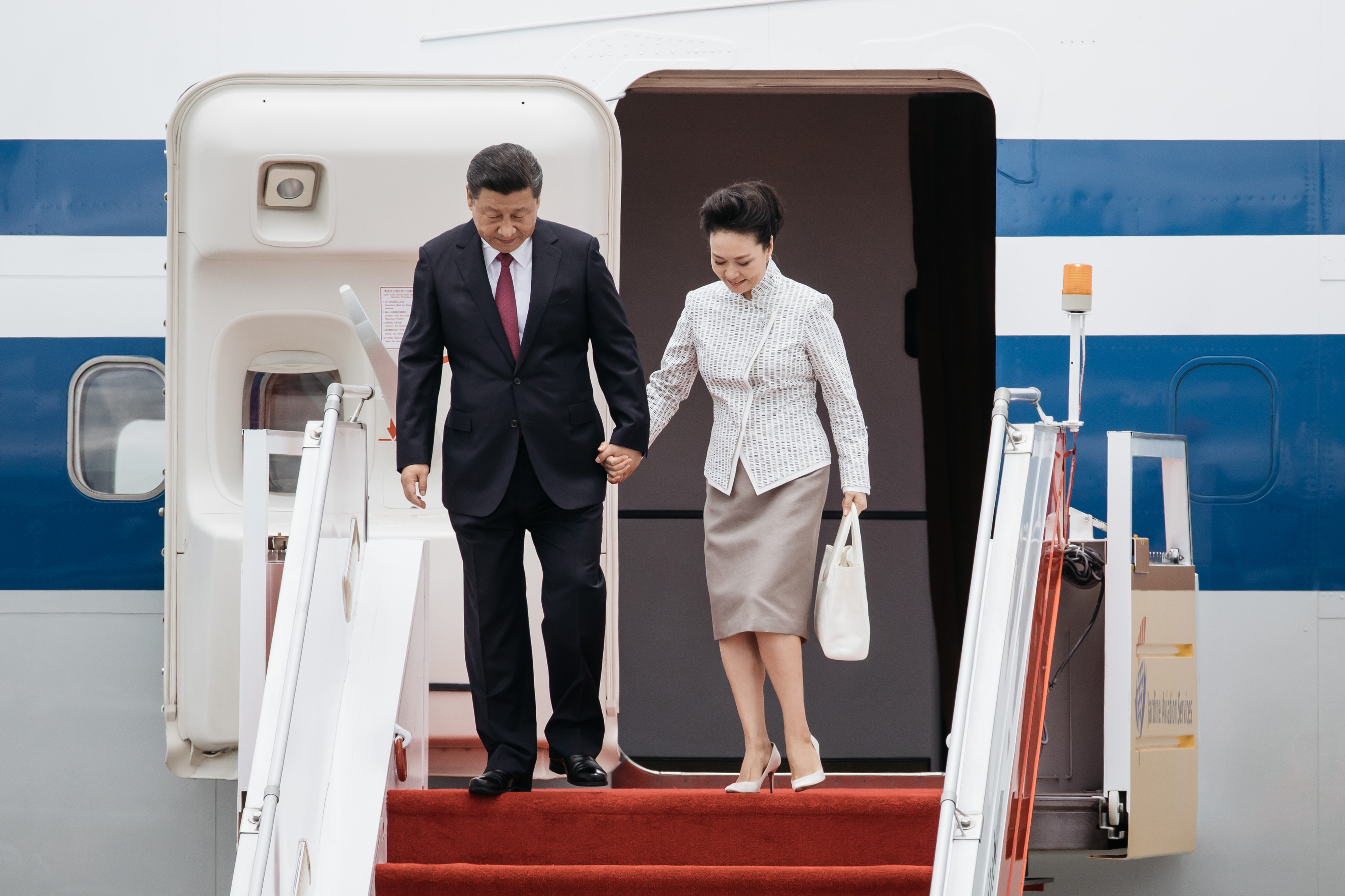Xi Jinping, China's president, left, and Peng Liyuan, China's first lady, disembark from a plane at Hong Kong International Airport in Hong Kong, China, on Thursday, June 29, 2017. Xi arrived Thursday for his first visit to the financial hub since becoming China's top leader in 2012.