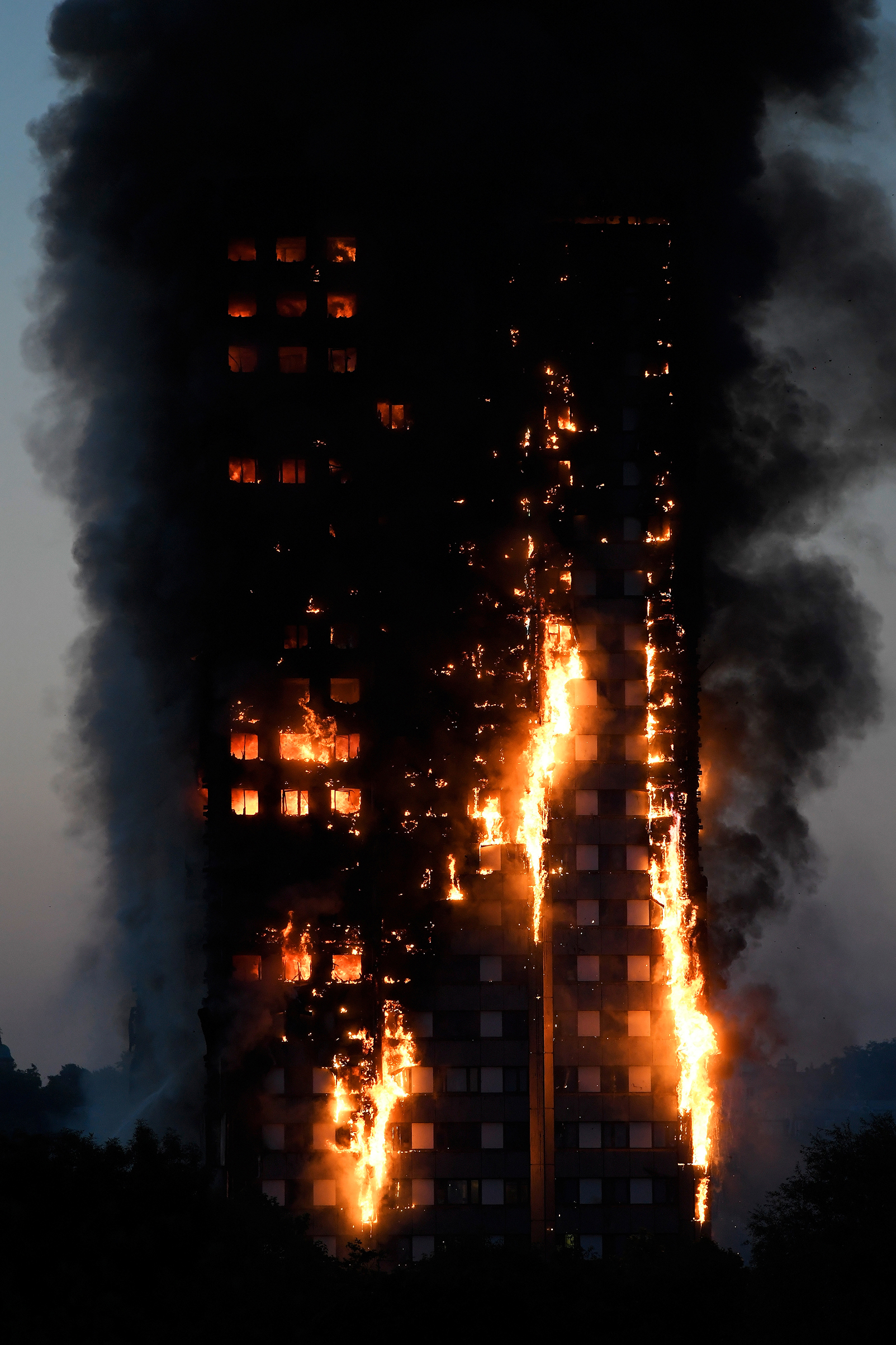 Flames and smoke billow as firefighters deal with a serious fire in a tower block at Latimer Road in West London on June 14, 2017.