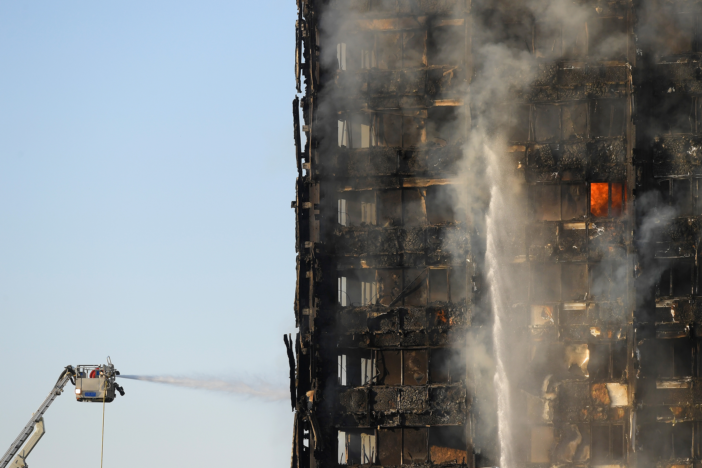 Firefighters spray water into the smoldering frame of a high-rise that caught fire overnight in West London on June 14, 2017.