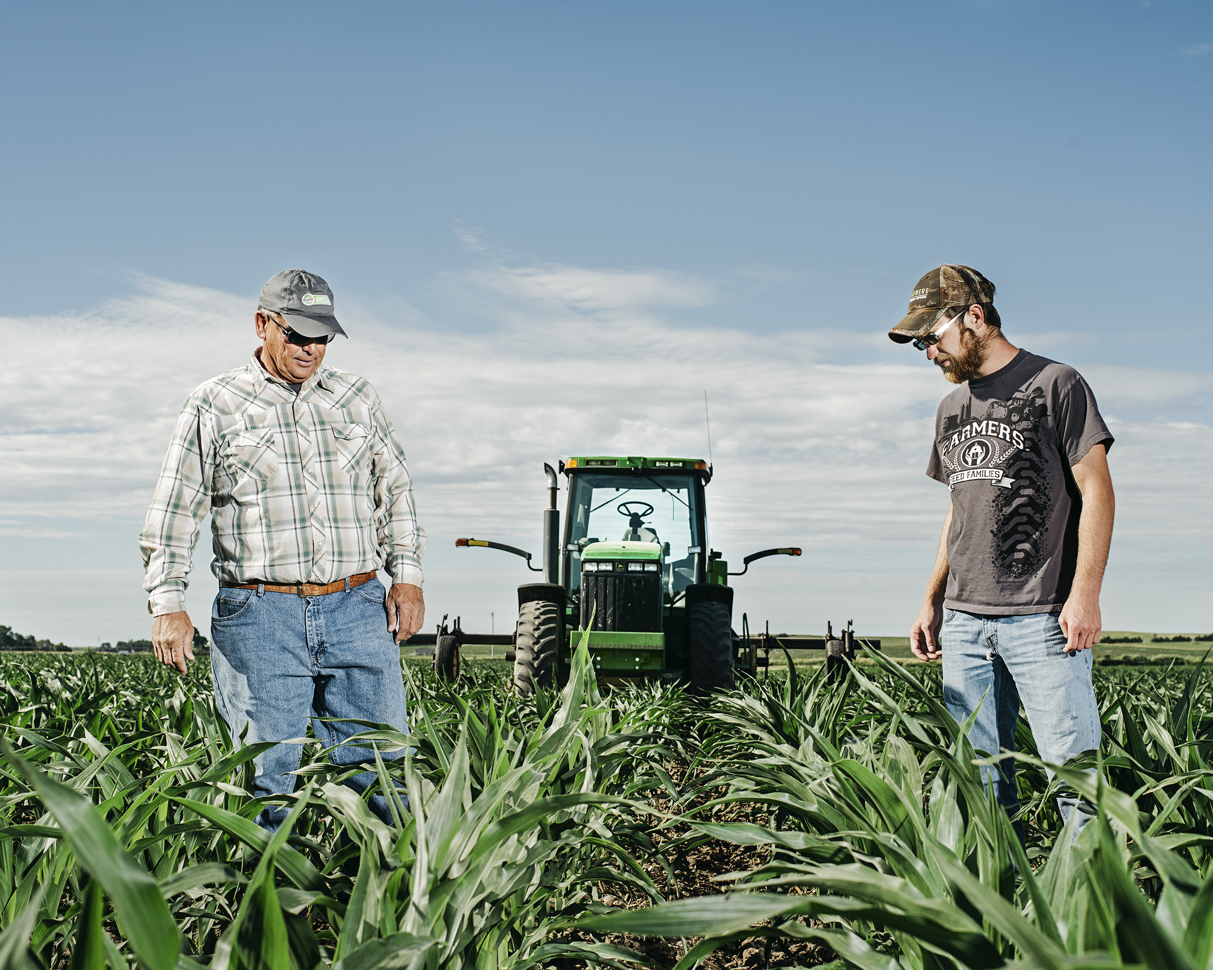 Guy Mills and his son James examine soil depth while hilling a cornfield with a John Deere tractor outside of Ansley, Neb., on June 19