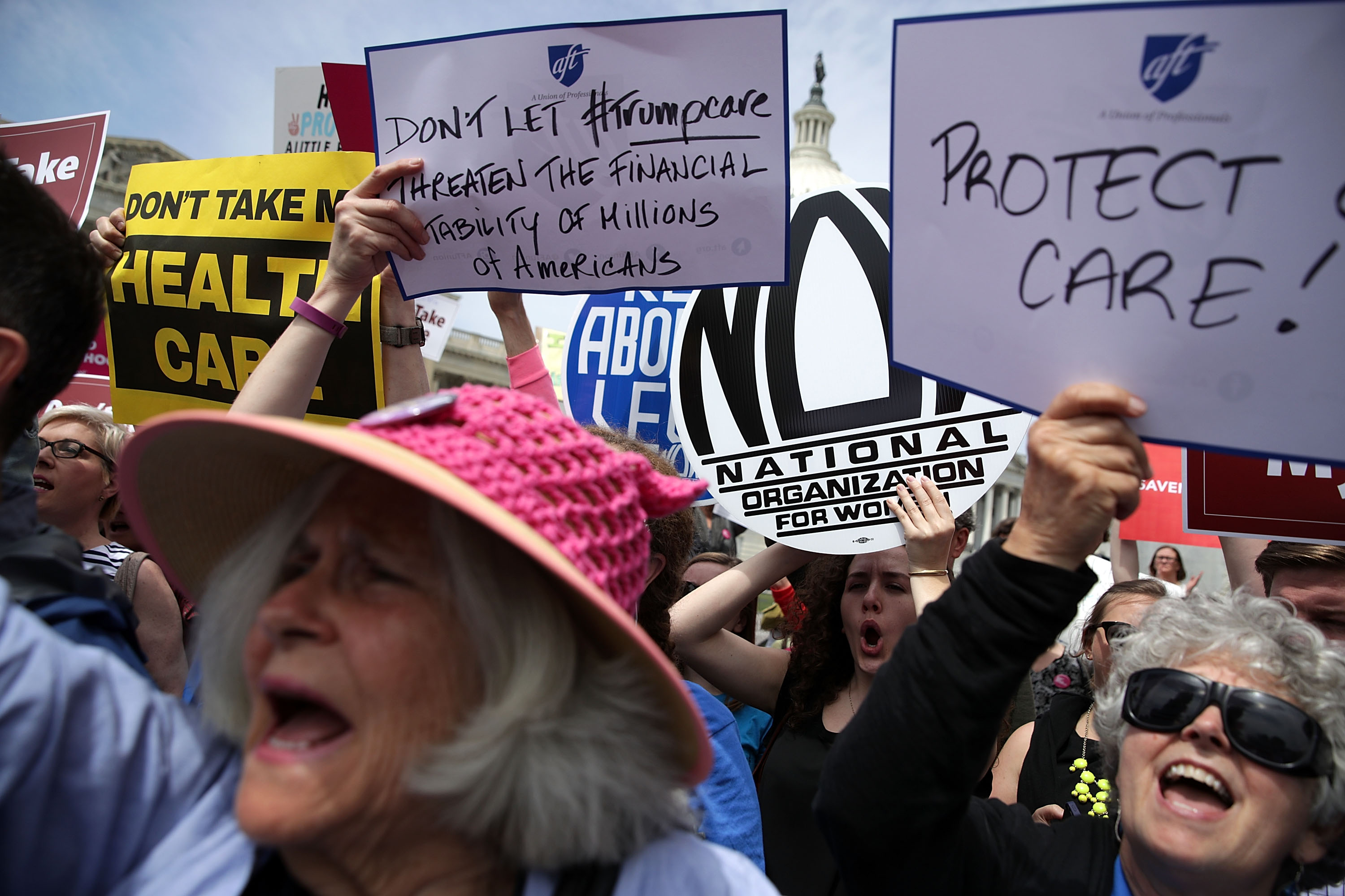 Activists hold signs during a Stop 'Trumpcare' rally May 4, 2017 in front of the Capitol in Washington, DC. Congressional Democrats joined activists for a rally to urge not to replace Obamacare, also known as the Affordable Care Act.