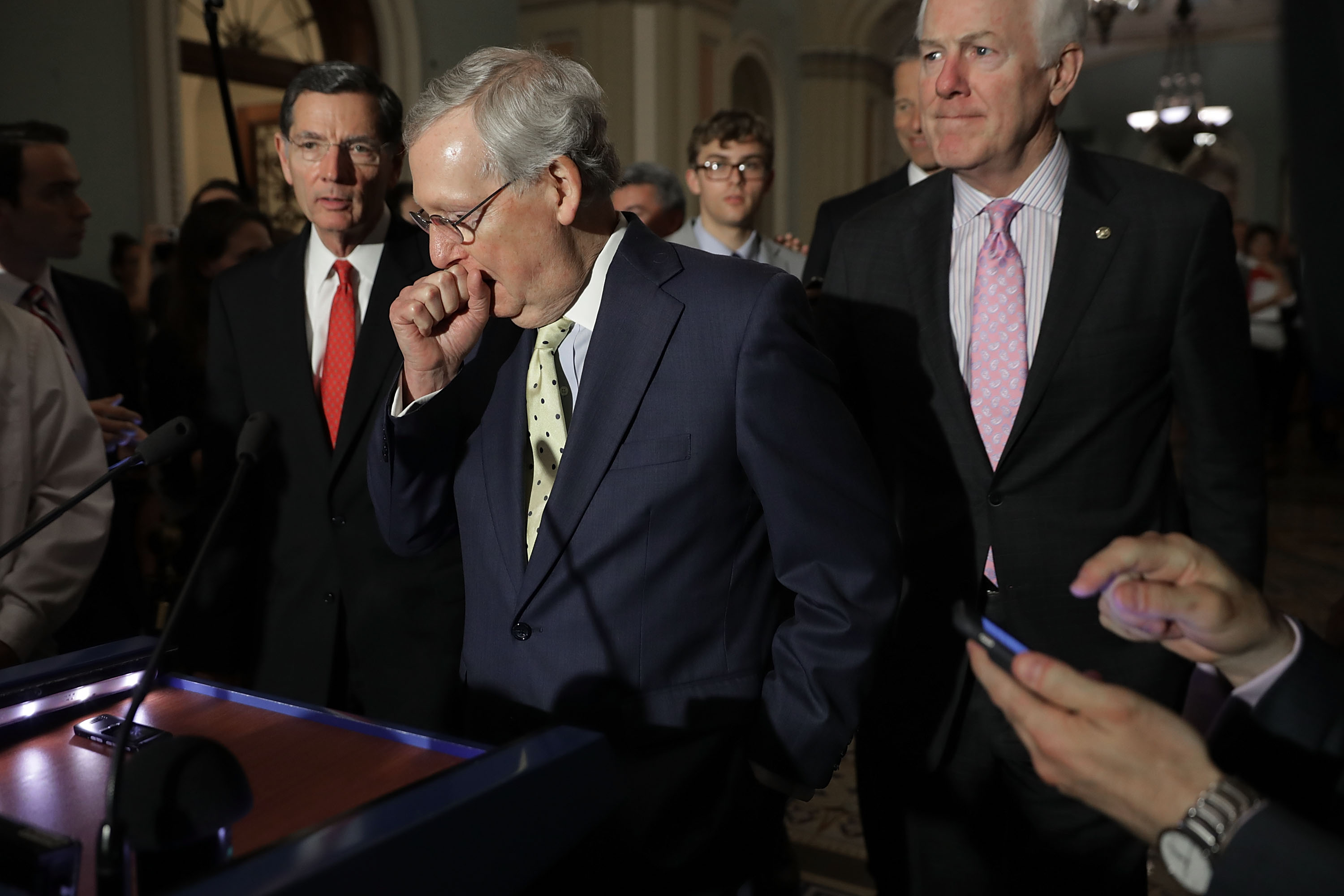 U.S. Senate Majority Leader Mitch McConnell (R-KY) (C) approaches the microphones before talking with reporters with Sen. John Barrasso (R-WY) (L) and Senate Majority Whip John Cornyn (R-TX) following the weekly GOP policy luncheon at the U.S. Capitol June 20, 2017 in Washington, D.C.