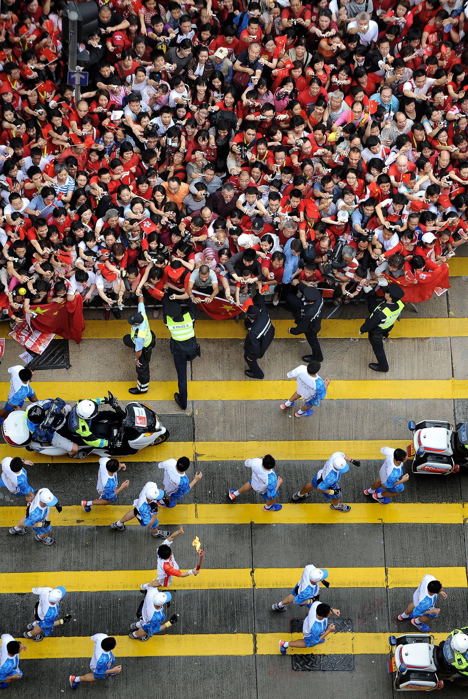 The Olympic torch, bottom, is paraded along Nathan Road in the Tsim Sha Tsui district of Hong Kong on May 2, 2008. Pro-Tibetan protesters, however, soured what should have been a patriotic moment for the authorities. Police detained around 20 people following minor scuffles along the route of the Olympic torch relay, as Hongkongers exercised their freedom to pile more pressure on China over Tibet and its human rights record.