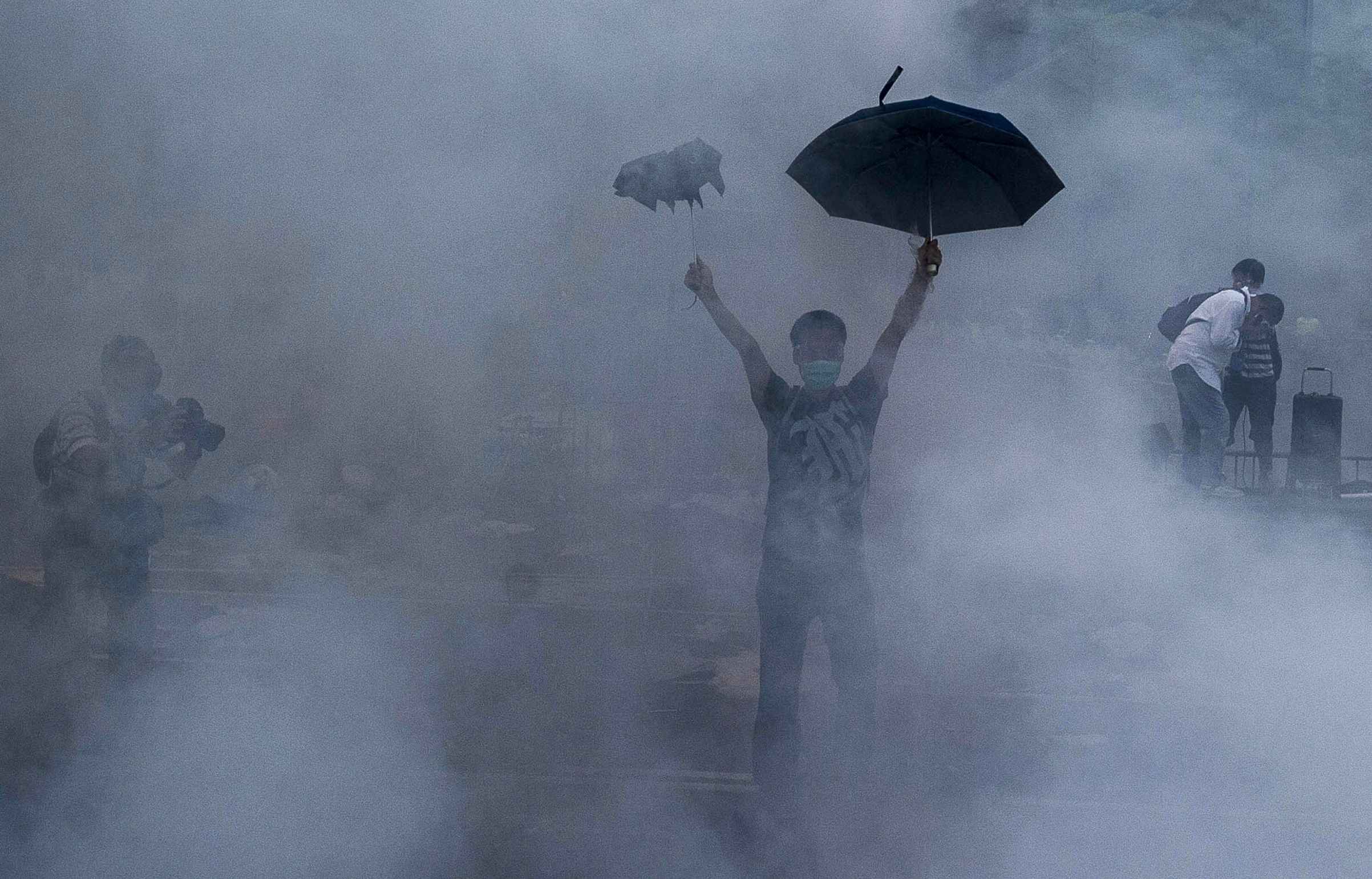 A pro-democracy demonstrator gestures after police fired tear gas towards protesters near the Hong Kong government headquarters on Sept. 28, 2014. The incident marked the birth of the 79-day Umbrella Revolution, named after the umbrellas that demonstrators used to shield themselves from police pepper spray. The movement saw tens of thousands of Hongkongers occupy the streets in a push for greater democracy and the right to freely chose the territory's leader.