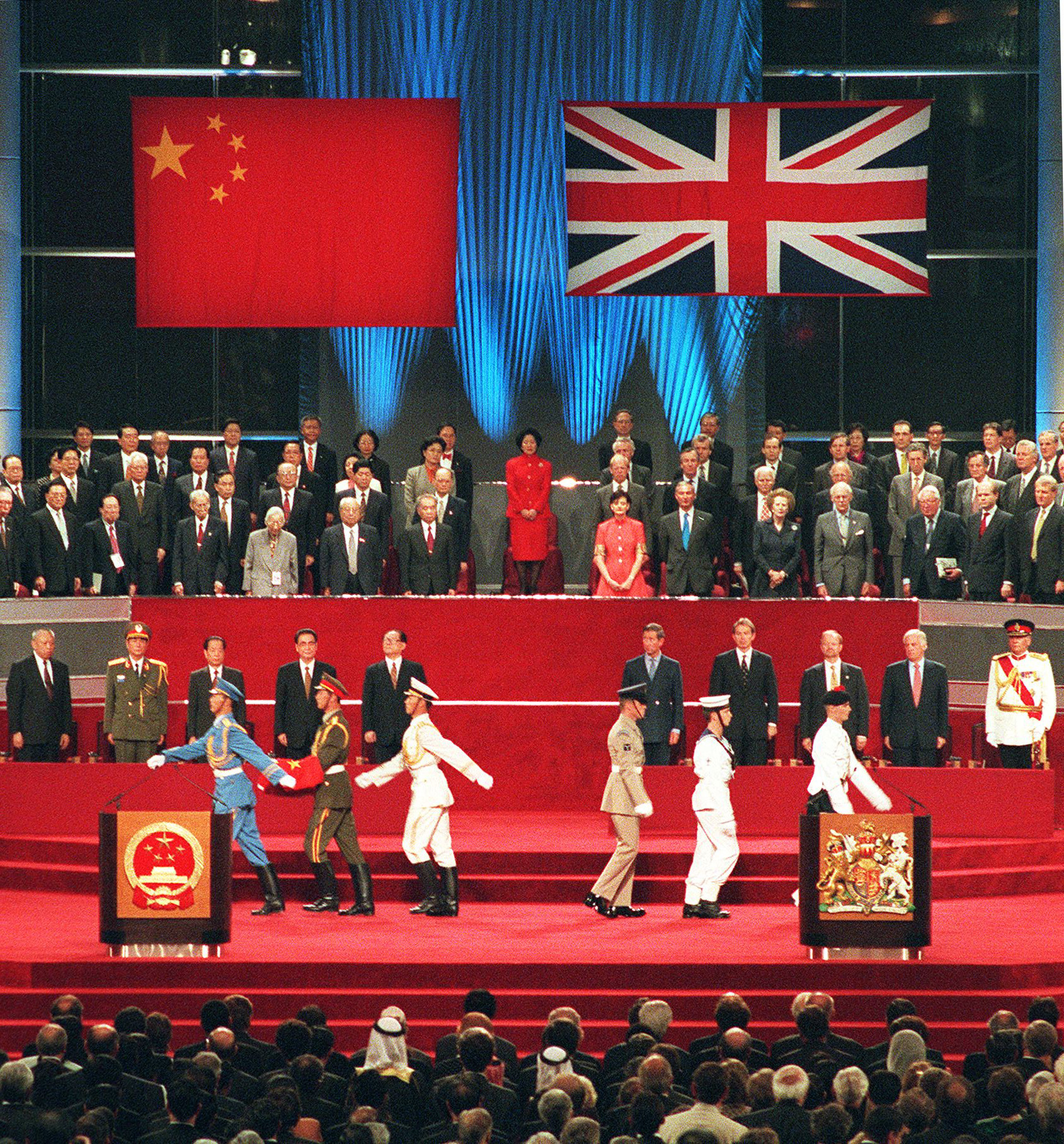 A Chinese soldier holds the national flag prior to its raising as the British military march, at right, during the handover ceremony at the Hong Kong Convention and Exhibition Centre on July 1, 1997. The event marked the end of 156 years of British colonial rule over the territory.