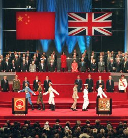 A Chinese soldier holds the national flag prior to its raising as the British military march, at right, during the handover ceremony at the Hong Kong Convention and Exhibition Centre on July 1, 1997. The event marks the end of 156 years of British colonial rule over the territory.