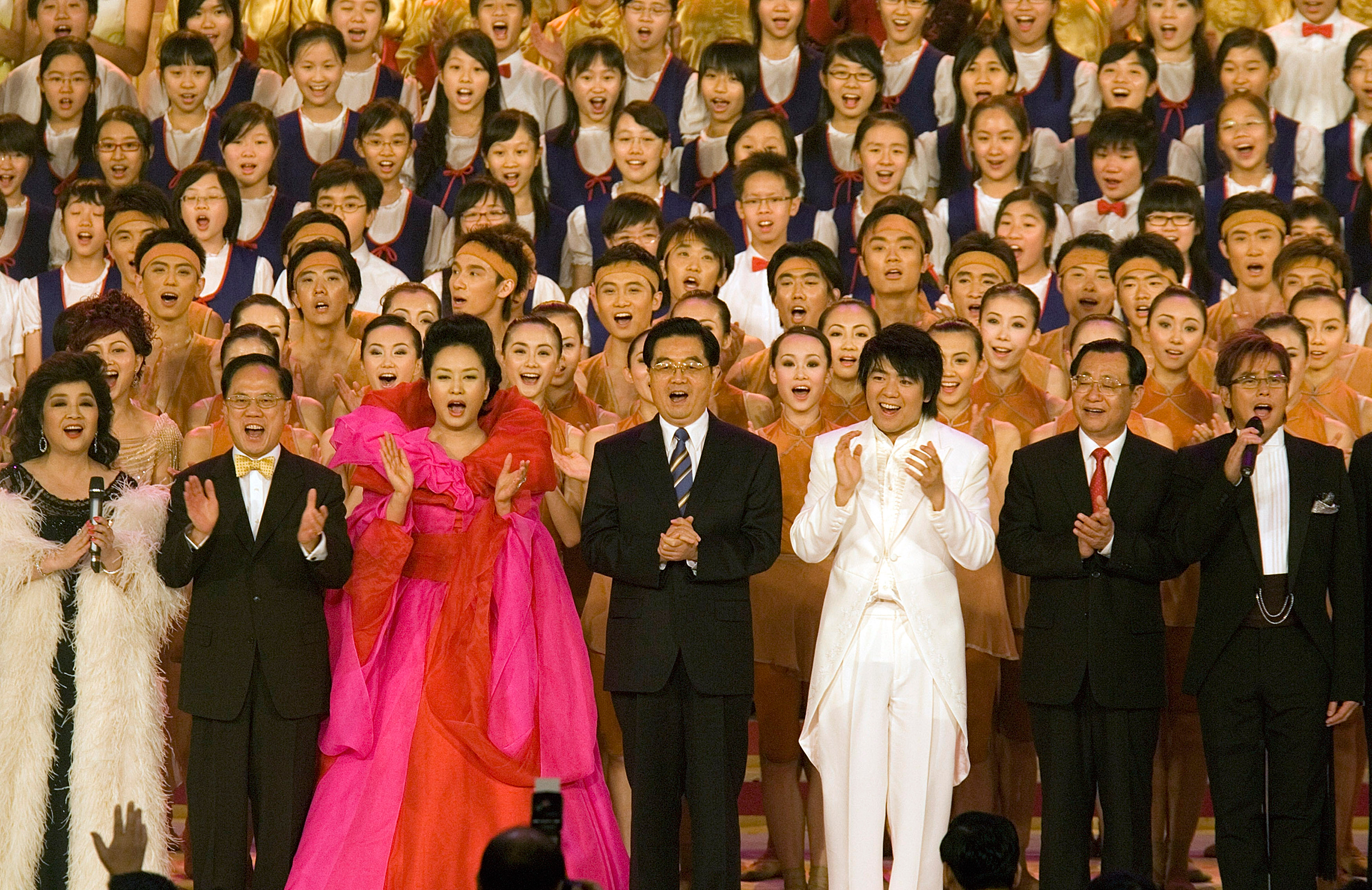 Chinese President Hu Jintao, center, sings on stage with performers at the conclusion of the Grand Variety Show in celebration of the 10th anniversary of the handover, in Hong Kong on June 30, 2007. Beneath the official cordiality, and outward prosperity, lay a city already worried about Beijing's encroachment on its freedoms and struggling to come to terms with its place in China. Many had started to regard China as an alien power and themselves as not Chinese but Hongkongers first and foremost.