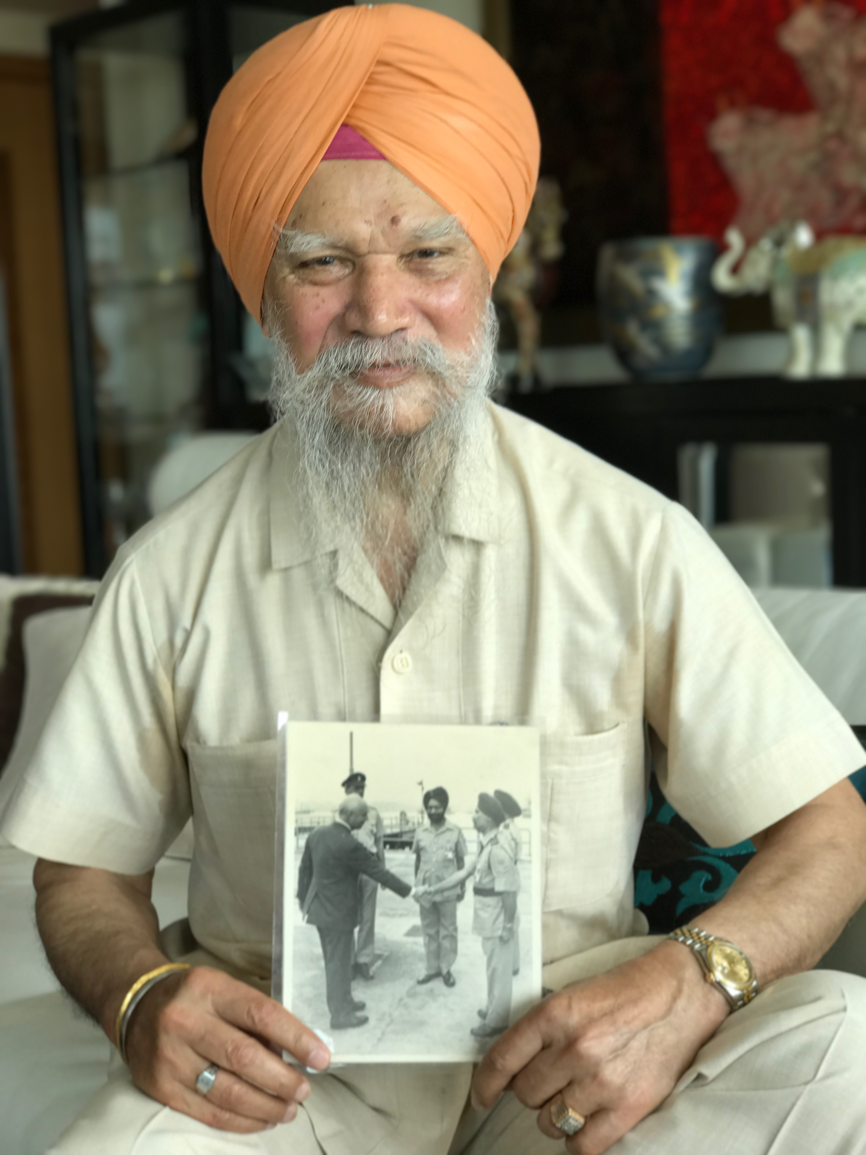 Gill Sukha Singh, 77, former president of the Sikh Temple, and a retired British Army serviceman, holds an undated photograph of himself greeting a former colonial governor, at his home in Park Island, Hong Kong, on June 22, 2017.  Hong Kong is my birthplace. My father was in the British Army and he married my mother here.  She was Chinese and spoke Cantonese to me. There were many such marriages. I joined the British army in June 1960 and retired in 1993 when my unit was disbanded. I was in the army depot police. Sikhs were employed to guard ammunition because we don't smoke. I've never thought of leaving. Punjabis have prospered here. Many of our children are professionals and people have beautiful homes. My son is the first person of Indian descent born here to become a doctor. This is our home. I consider myself a Hong Kong person.