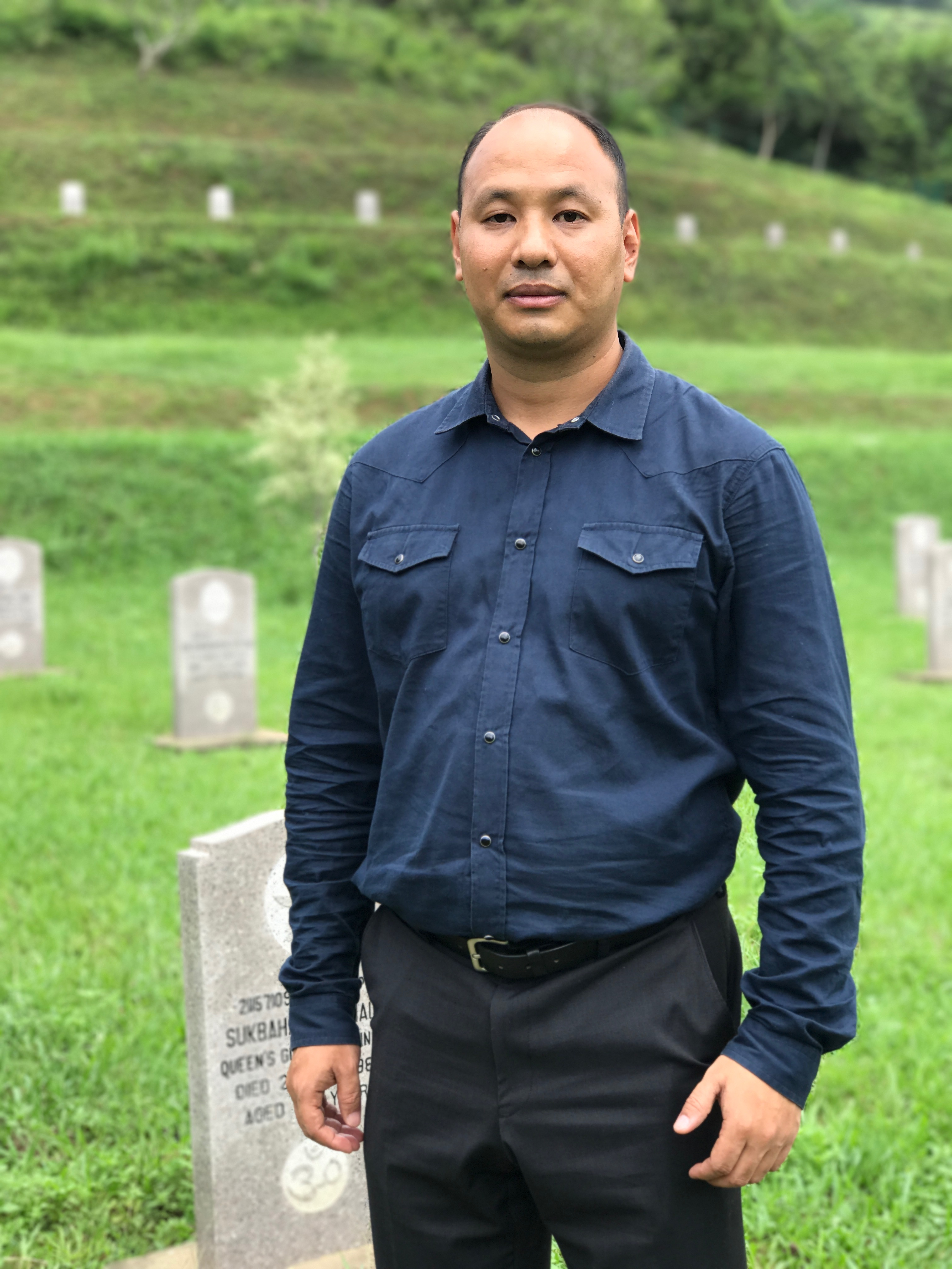 "Amod Rai, age 37, a teacher and activist for the Gurkha community, pictured at the cemetery for Gurkha servicemen in San Tin, Hong Kong, on June 22, 2017. ""The Nepalese community is a part of Hong Kong history and 80% of the community consists of Gurkha descendents. We started coming here in 1948, after World War 2, and we made the utmost contribution in making Hong Kong a safe place. Gurkhas cleared Hong Kong of wartime mines. They helped to build our infrastructure — bridges and roads and water supplies. They reforested the hillsides and they helped when disasters like typhoons struck. They maintained peace between the PLA and the British on the border.  None of this is in the Hong Kong school curriculum — our identity, dignity and culture are not included. People are calling for democracy. Well, diversity is a core element of that. If we want Hong Kong to be differentiated from China then we have to appreciate our diversity."""