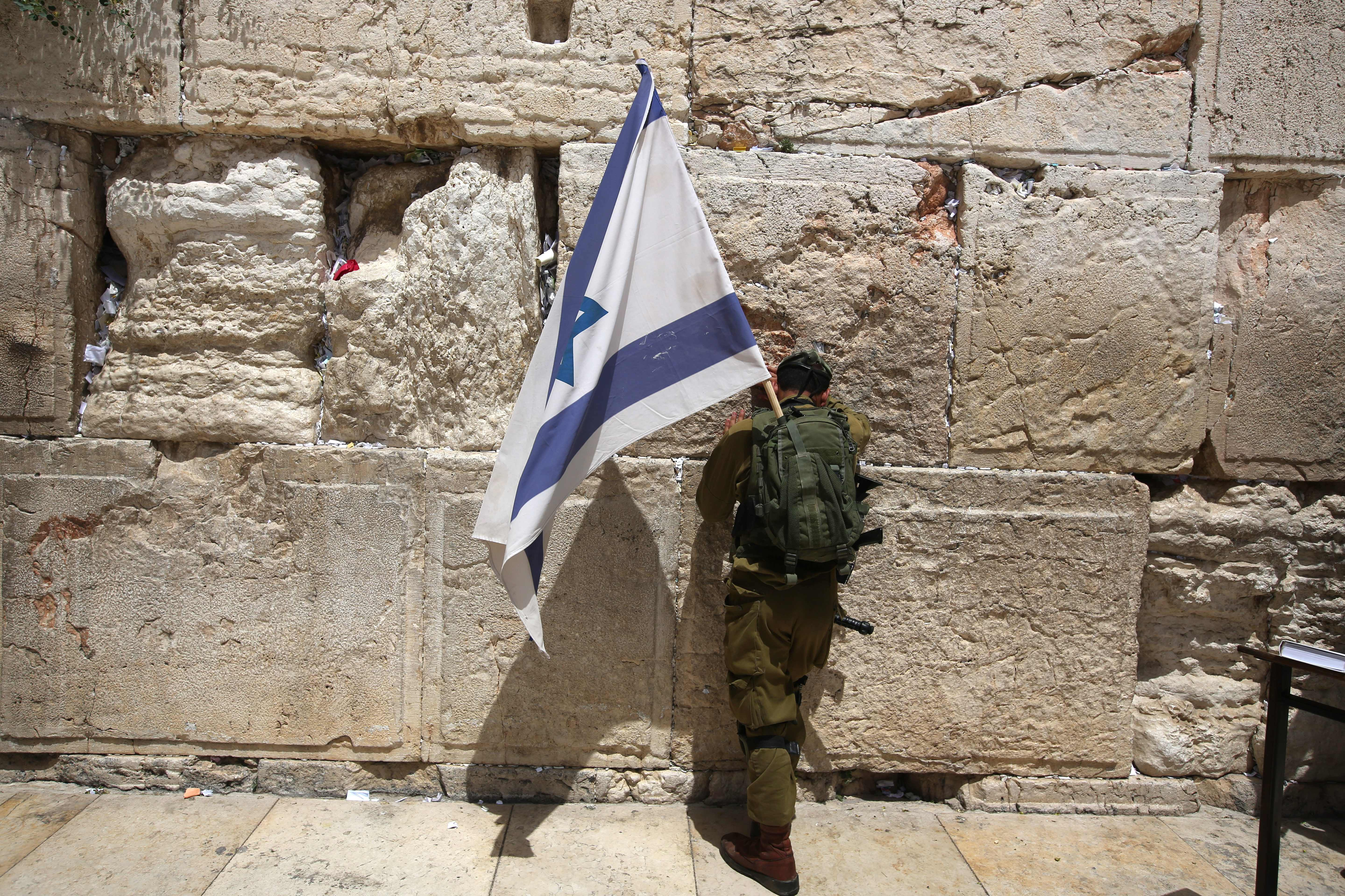 An Israeli soldier prays at the Western Wall with a national flag on June 5, 2016 in Jerusalem's old city, as Israelis celebrate Jerusalem Day.