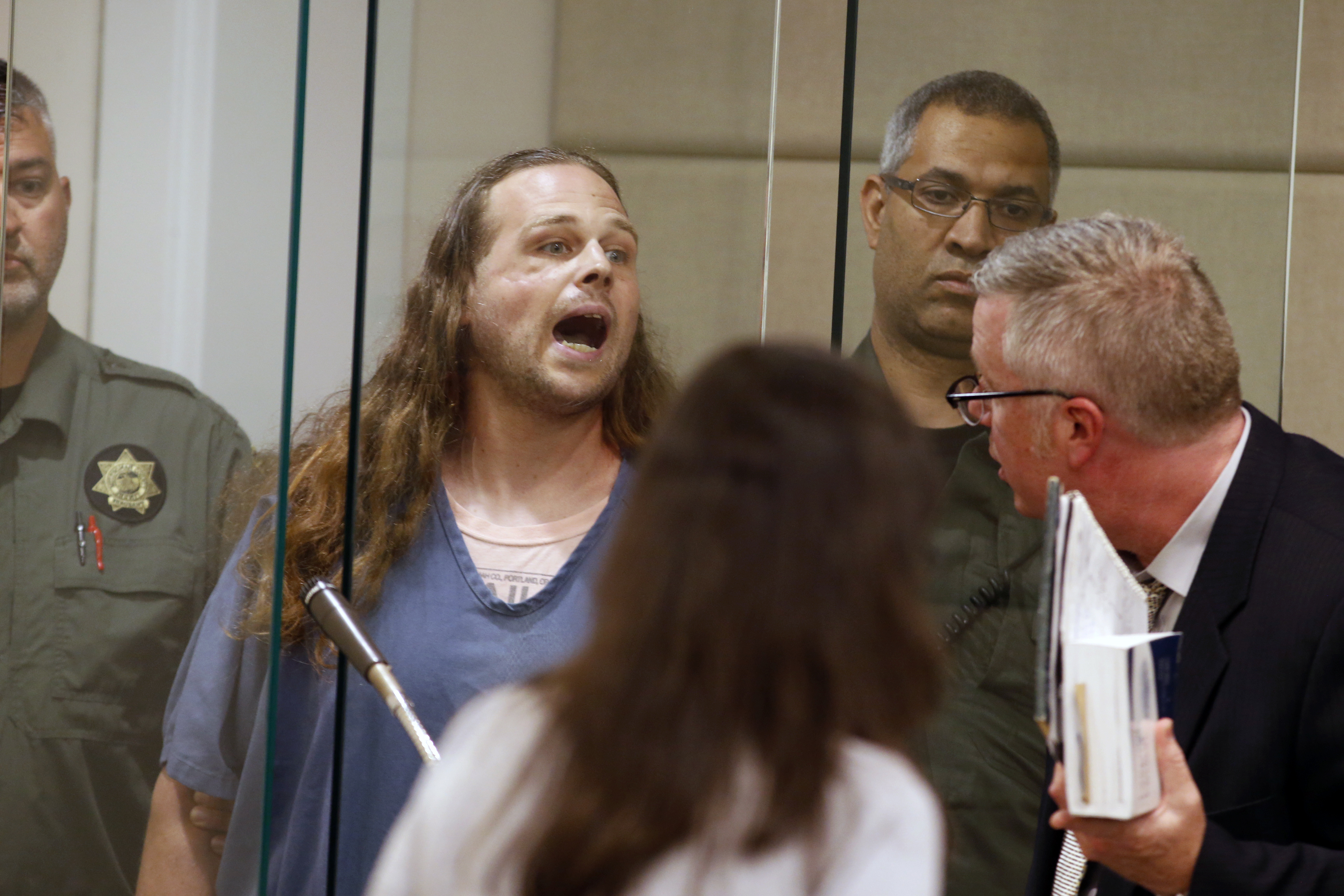 Jeremy Joseph Christian shouts as he is arraigned in Multnomah County Circuit Court in Portland, Ore., Tuesday, May 30, 2017. Authorities say Christian started verbally abusing two young women, including one wearing a hijab. When three men on the train intervened, police say, Christian attacked them, killing two and wounding one.