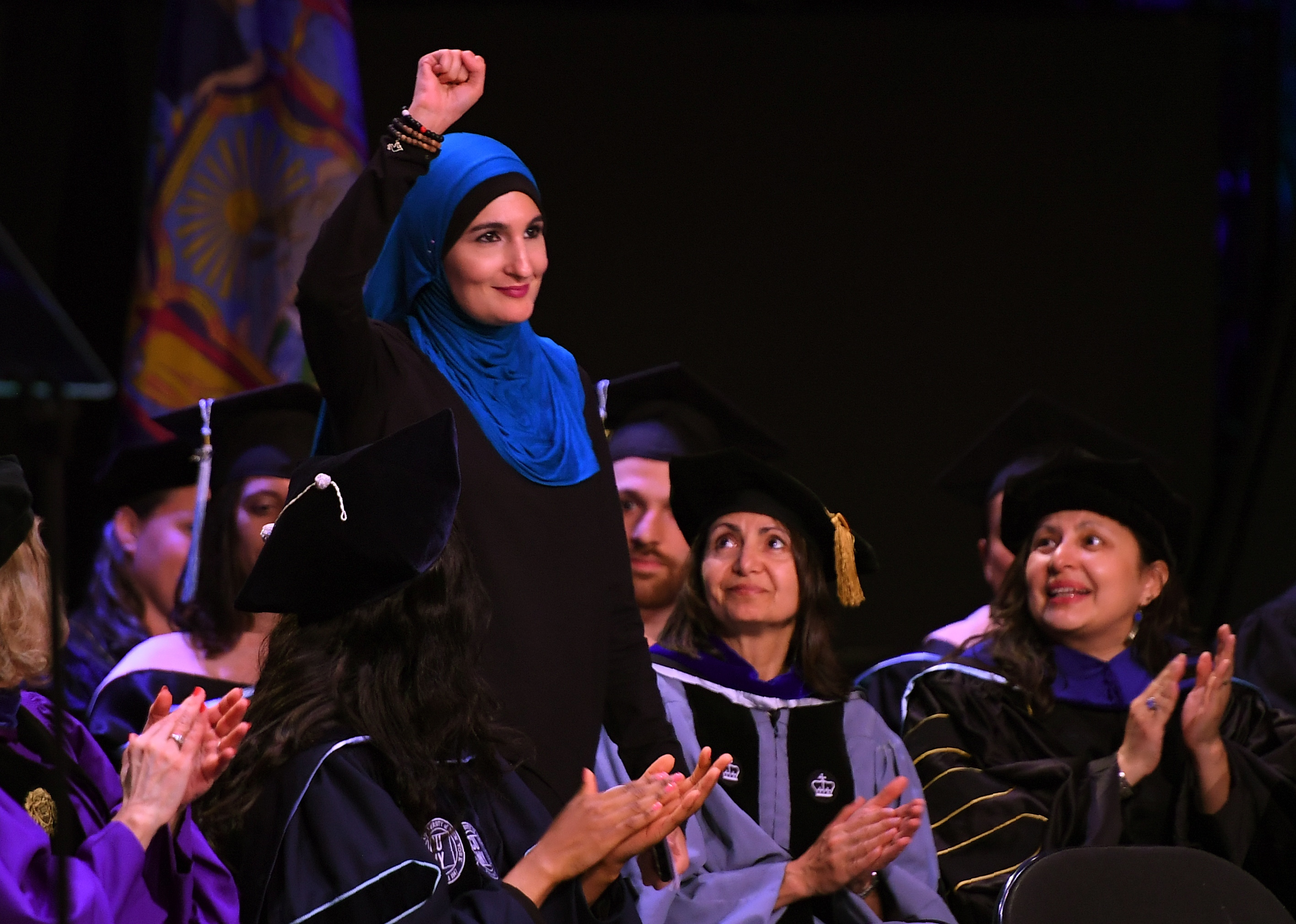Linda Sarsour, co-organizer of the National Women's March, raises her fist as she walks to the stage to deliver the keynote address at the CUNY School of Public Health commencement ceremony on June 1, 2017 at the Apollo Theatre in Harlem.