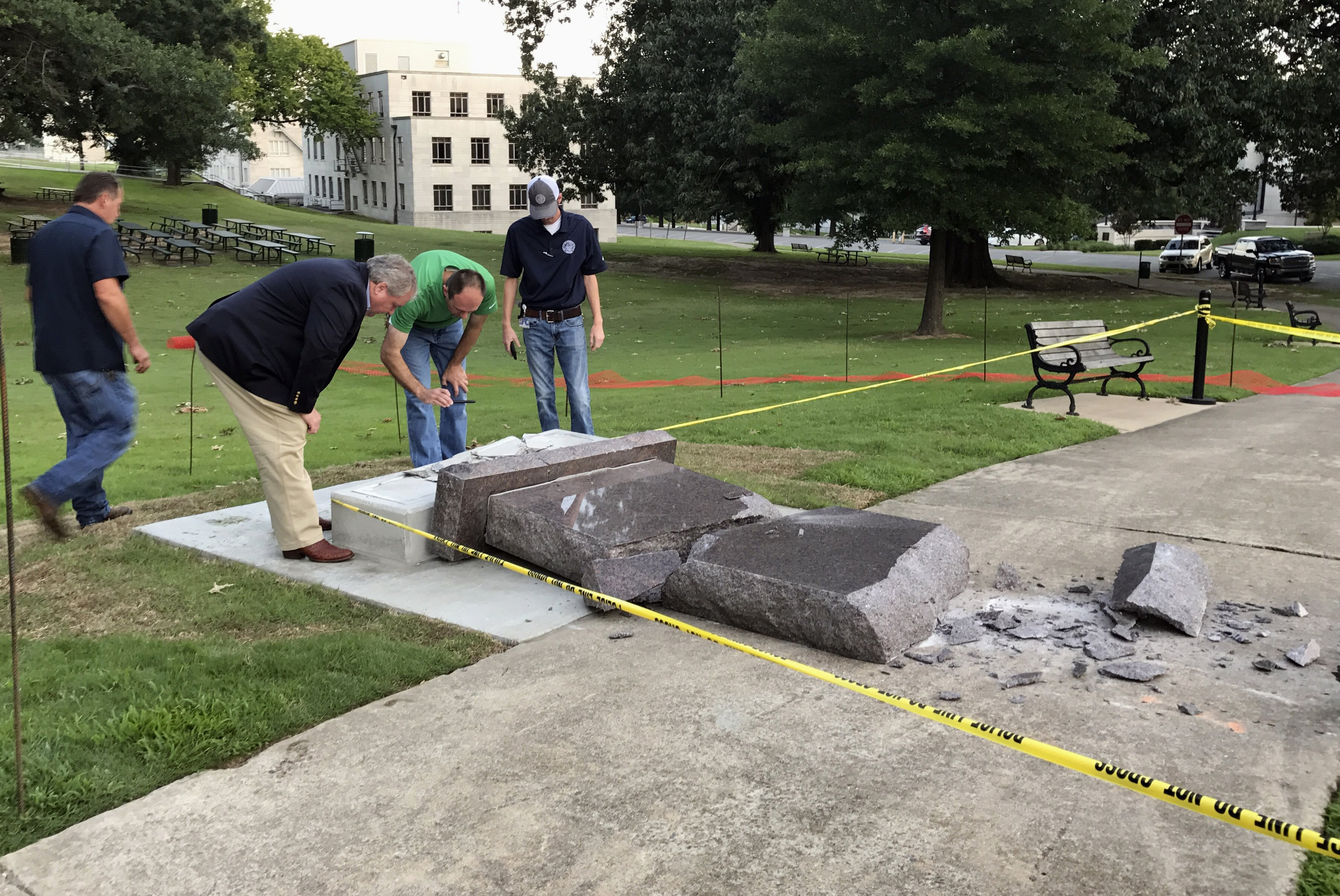Personnel from the Secretary of State's office inspect the damage to the new Ten Commandments monument outside the state Capitol in Little Rock, Ark., on June 28, 201.
