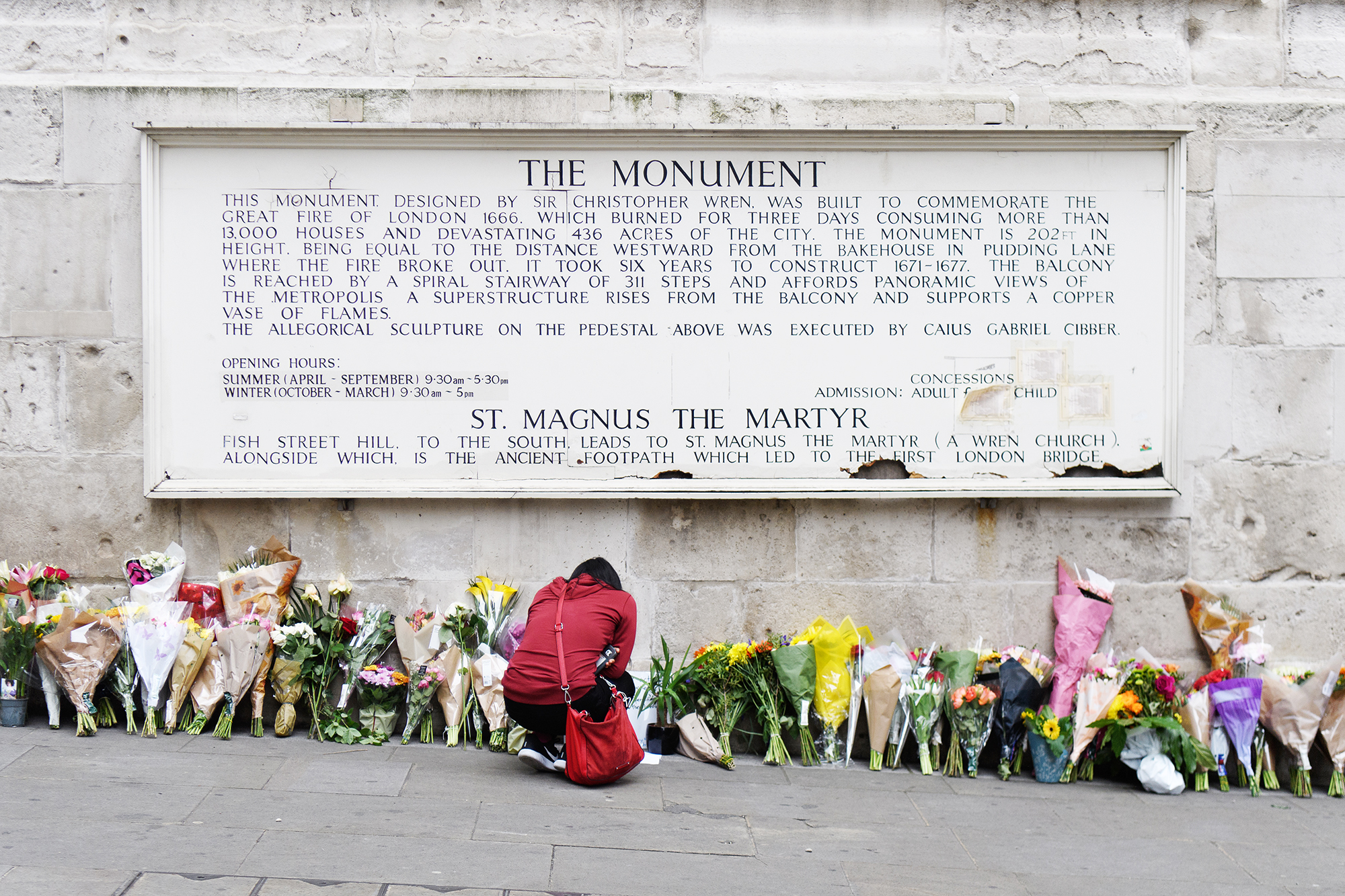 A woman looks at some of the floral tributes at Monument, near London Bridge, on June 5, 2017.
