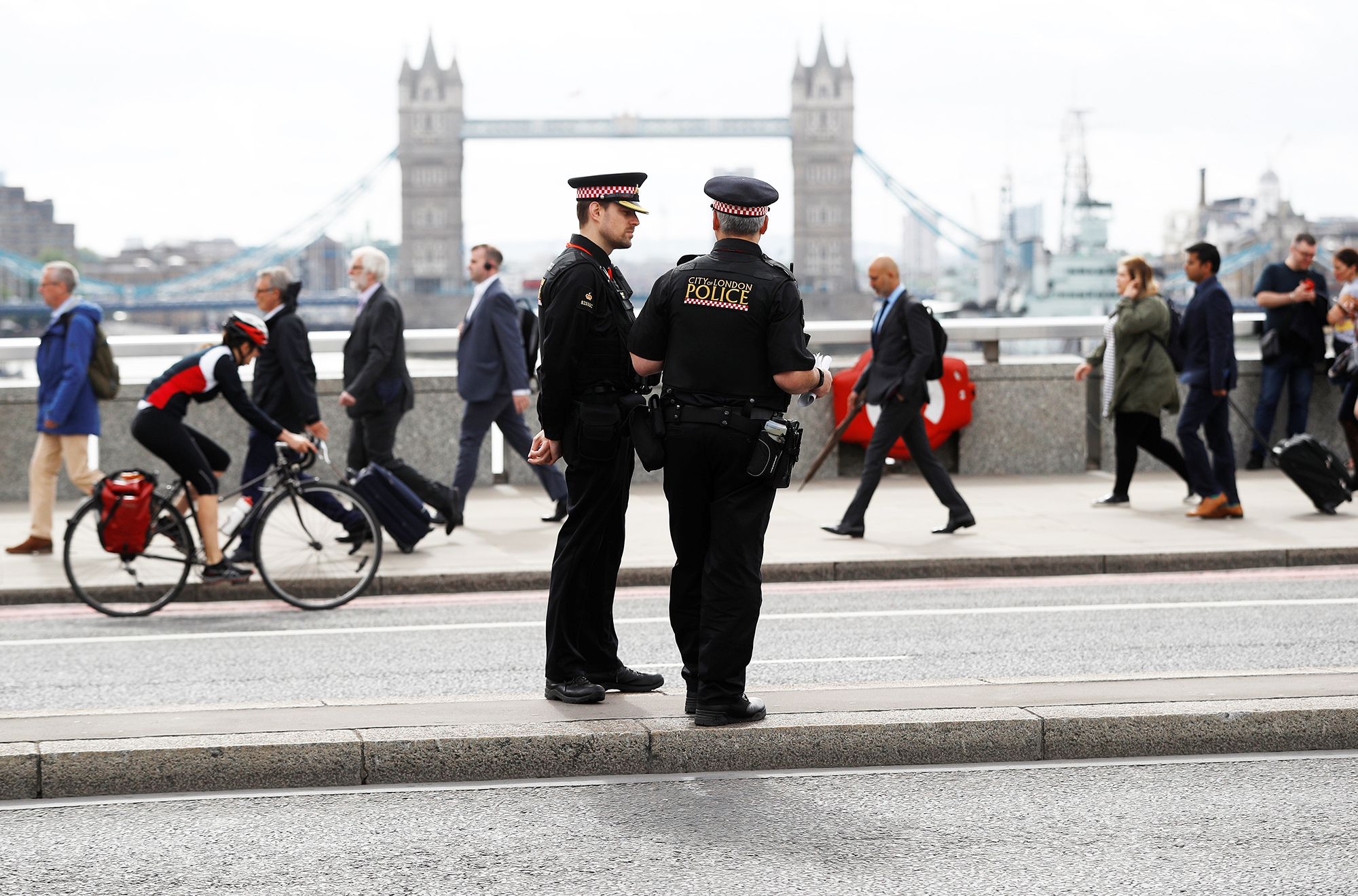 Commuters travel past City of London police officers, standing on London Bridge, after is was reopened in central London, on June 5, 2017.