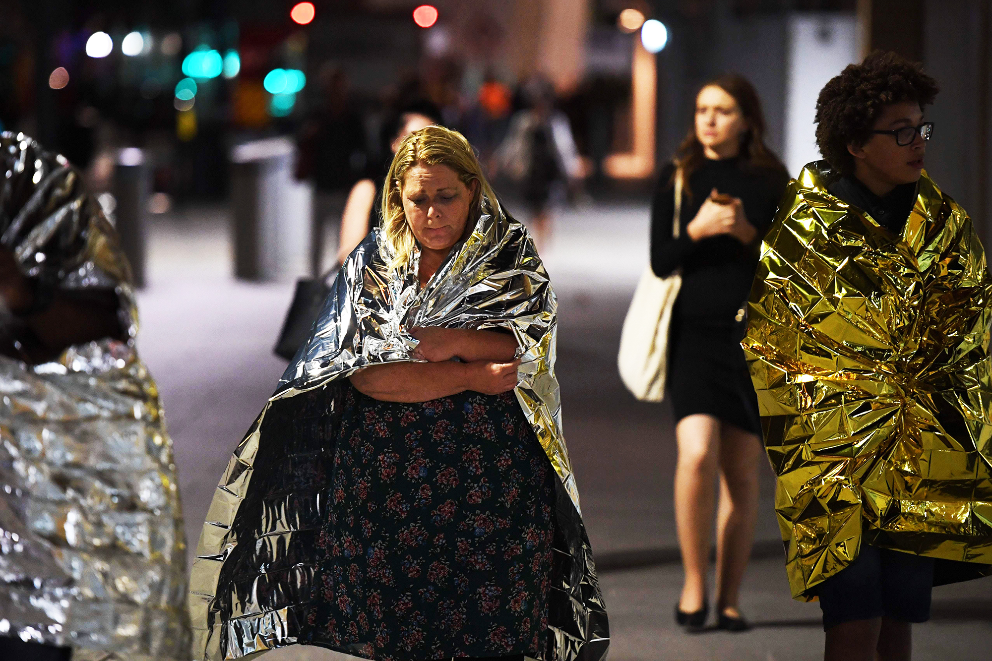 Bystanders, wrapped in emergency blankets leave the scene of a terror attack on London Bridge in central London, on June 3, 2017.