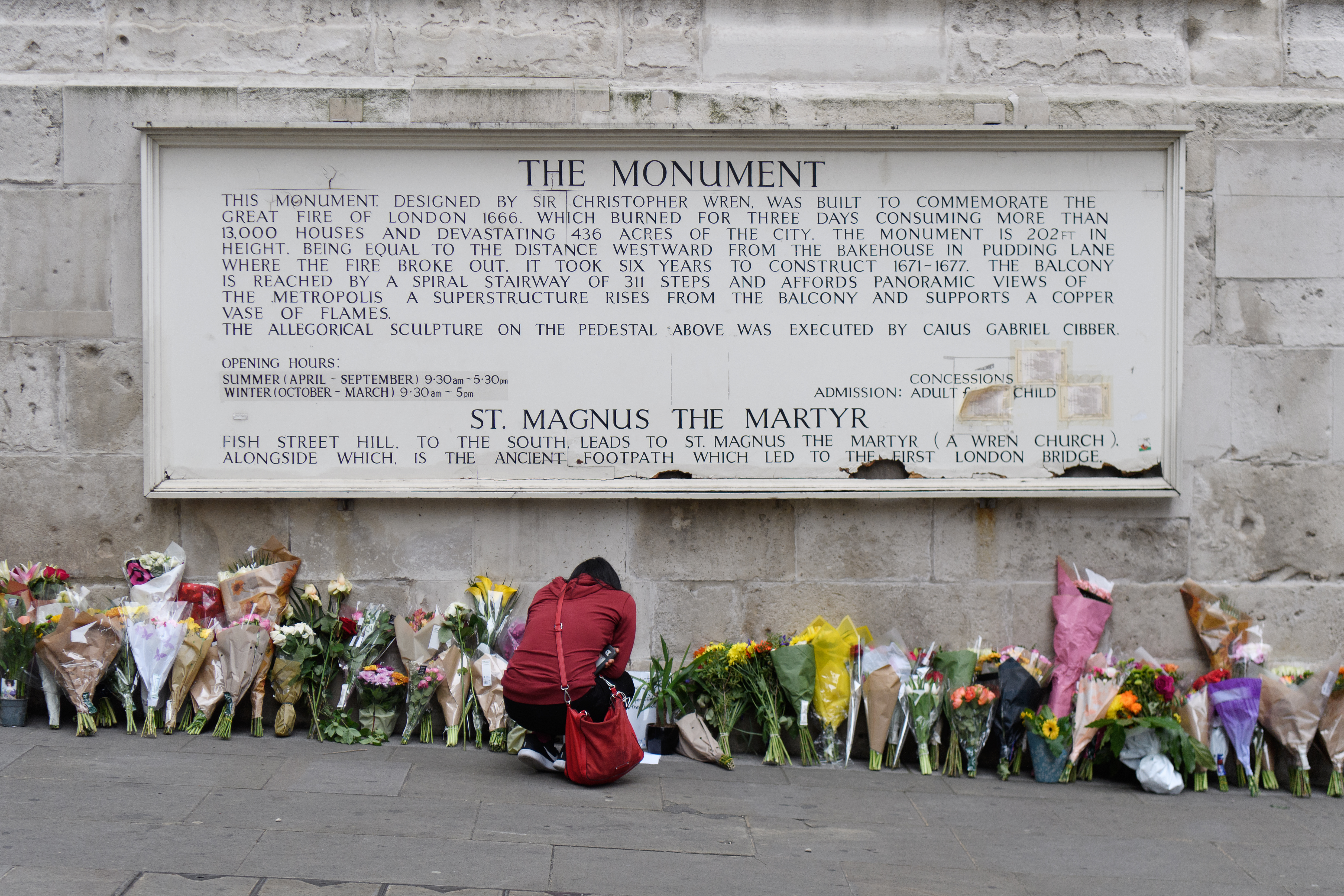 A woman looks at some of the floral tributes at Monument, near London Bridge, following the June 3rd terror attack on June 5, 2017 in London, England.