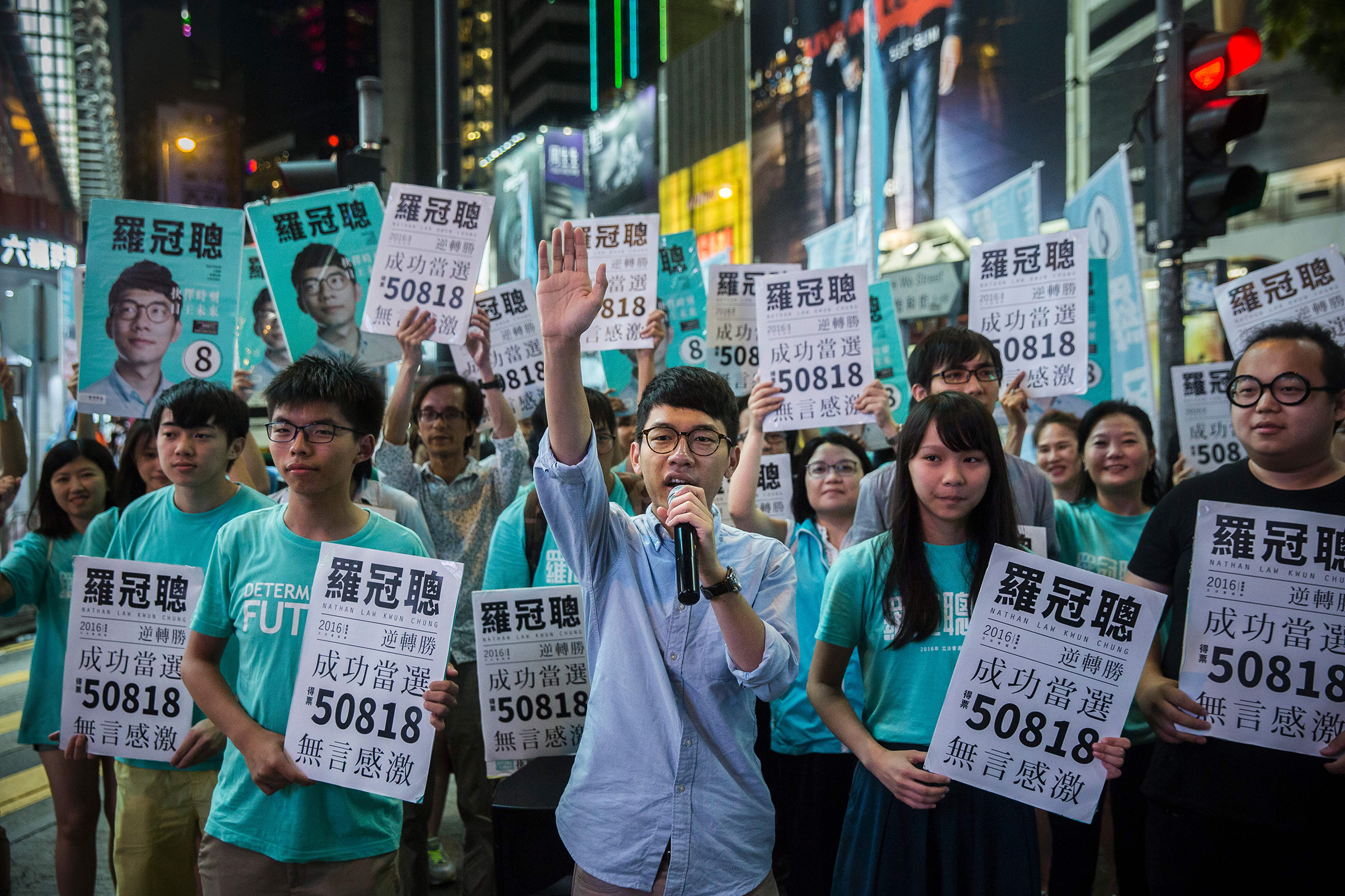 Nathan Law, center, speaks at a rally with Jousha Wong, to his right, and supporters in Causeway Bay following Law's win in the Legislative Council election in Hong Kong on Sept. 5, 2016. Hong Kong's youngest ever legislator at the age of 23, Law represented a new generation of Hongkongers advocating a break from Beijing.