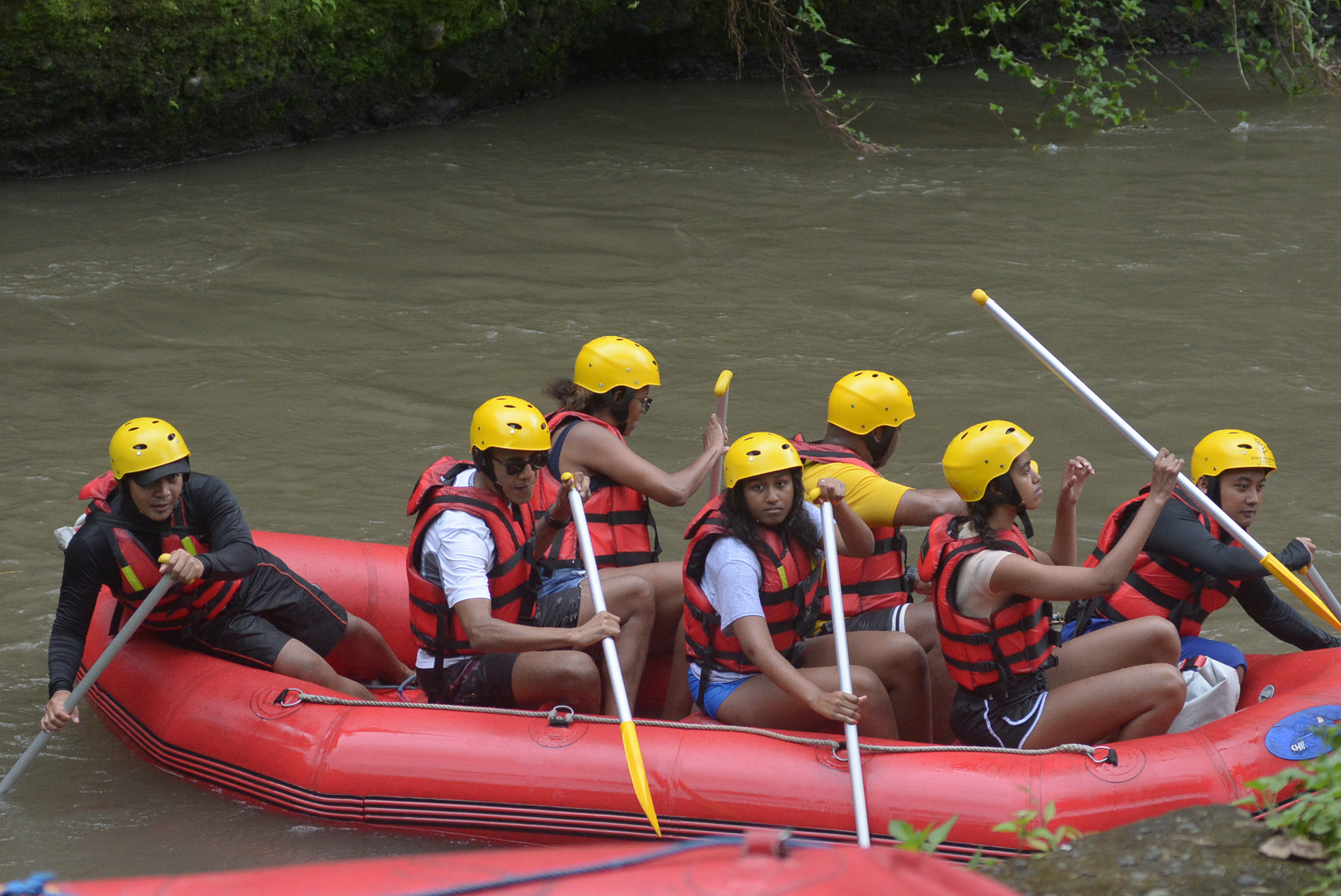 Former US president Barack Obama (2nd L), his wife Michelle (3rd L) and his daughters Sasha (front C) and Malia (2nd R) go rafting at Bongkasa Village in Badung on Bali island on June 26, 2017.