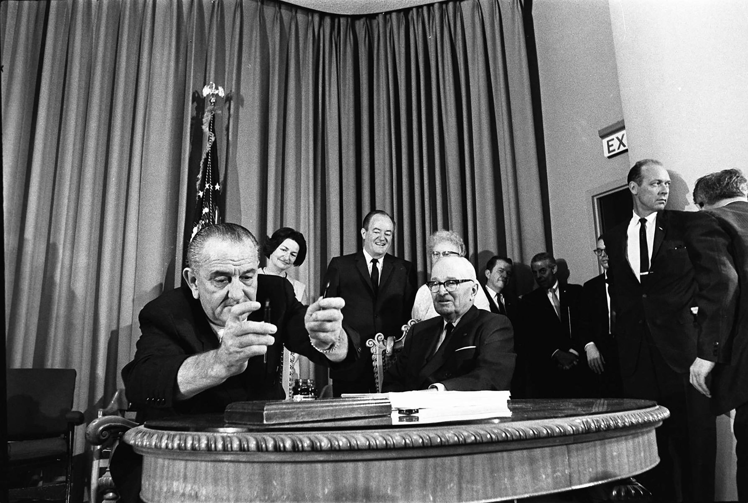 President Lyndon Johnson signs legislation creating Medicare and Medicaid in 1965.