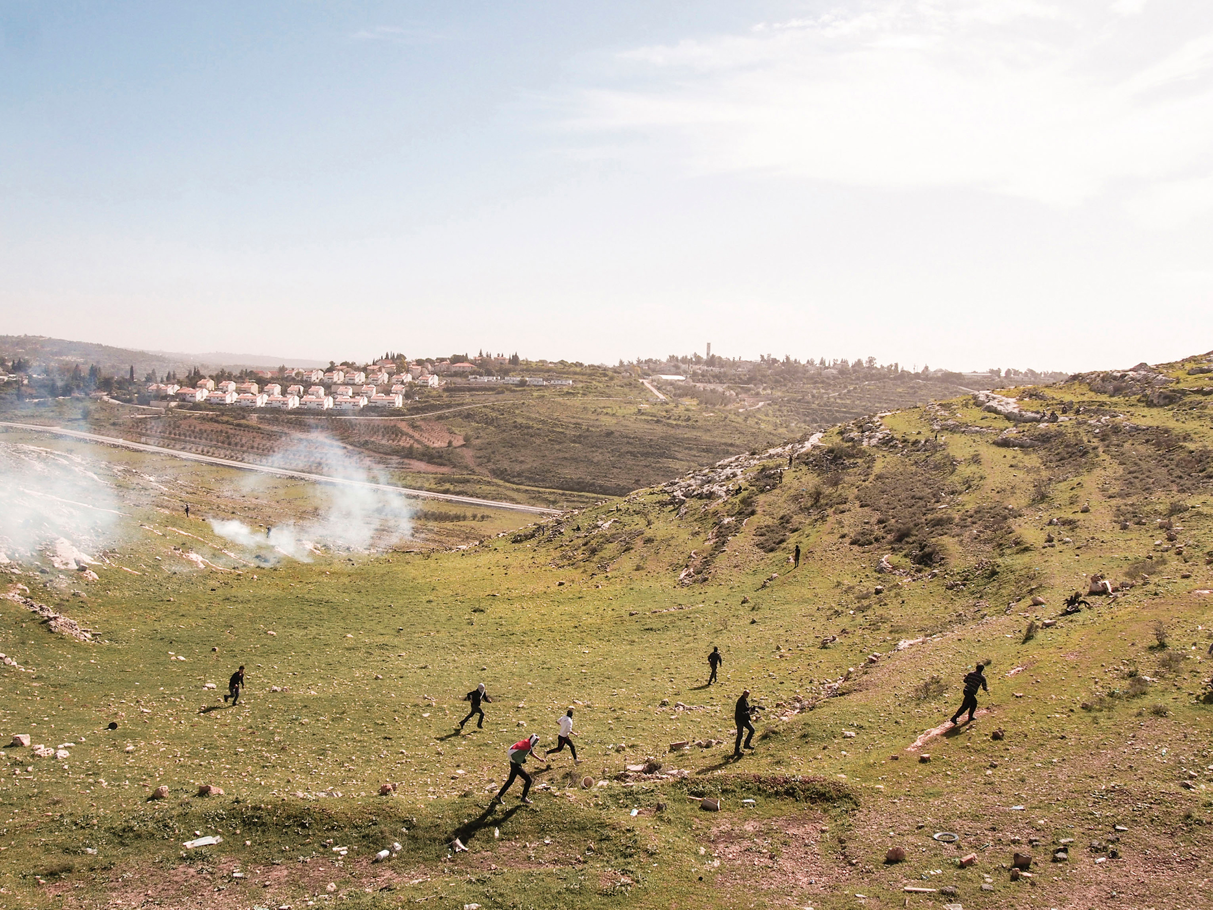 Palestinian protestors run from tear gas fired by Israeli soldiers at a weekly protest against the Israeli occupation. Nabi Saleh, West Bank, 2013.