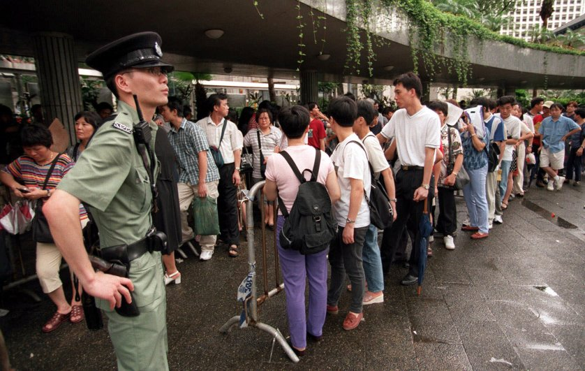 Mainland Chinese immigrants line up outside Hong Kong's Legislative Council building on July 8, 1999, to register their information to appeal for their residency rights in Hong Kong after the People's National Congress in Beijing provided a new interpretation of the Basic law. A Chief Judge admitted recent events in the right-of-abode affair had created confusion and he was unable to deal with a case of a mainland-born woman claiming the right to stay, the first to come before the court of Appeals since the re-interpretation of the Basic Law.