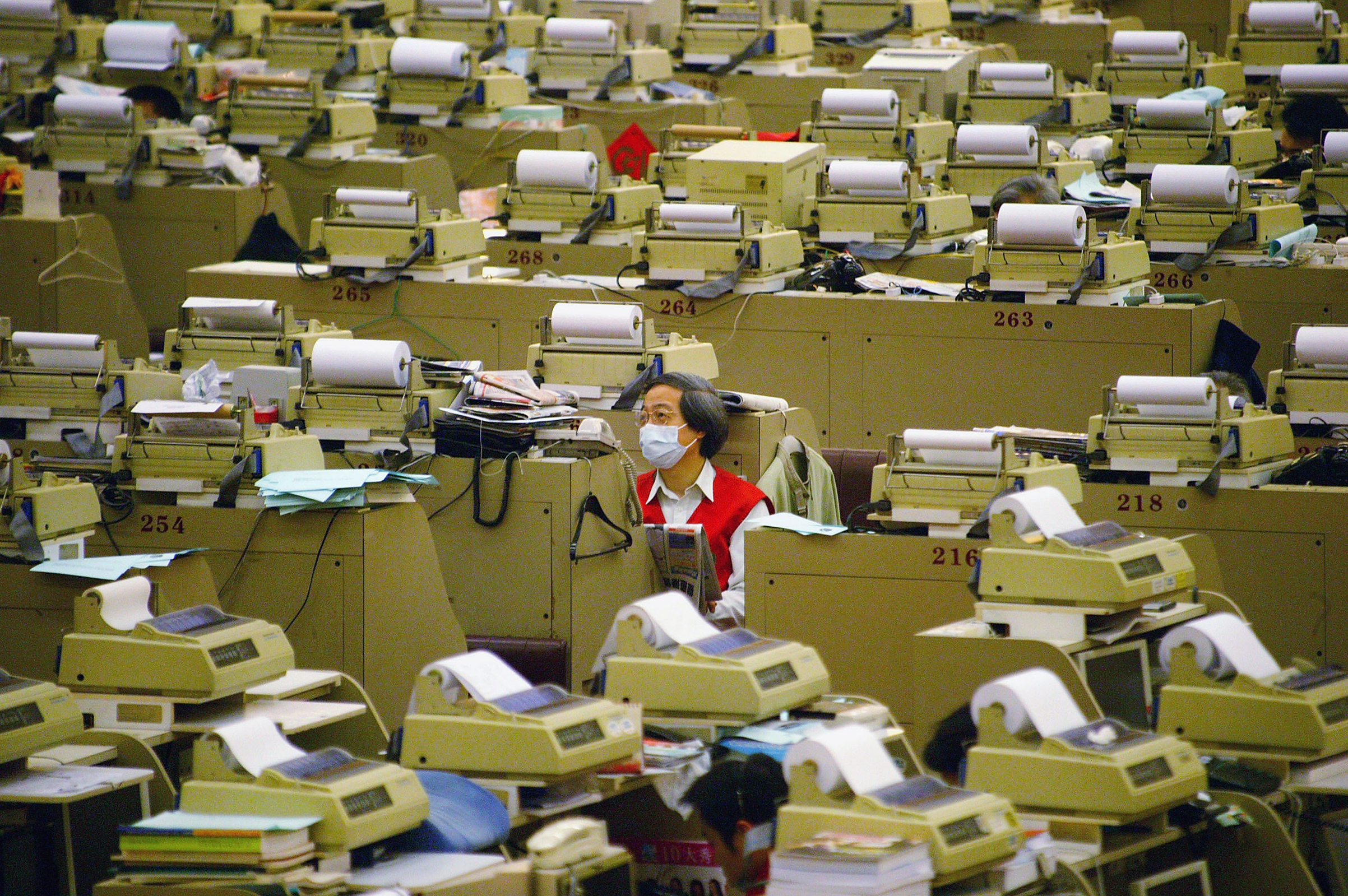 A trader on the stock exchange floor wears a protective mask against the SARS virus in Hong Kong on April 17, 2003. Some 300 people died of Severe Acute Respiratory Syndrome in Hong Kong — the highest toll in the global outbreak. For weeks, the city lived under a pall of fear. Hotels and restaurants were deserted, and masks and disinfectant became commonplace, as the population struggled to contain the outbreak.
