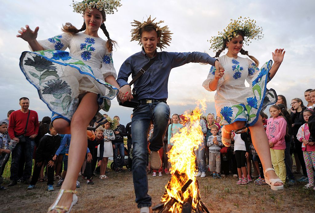Young people jump over a bonfire as they take part in the Ivan Kupala Night celebration, a traditional Slavic holiday, outside the small town of Turov, on July 6, 2016.