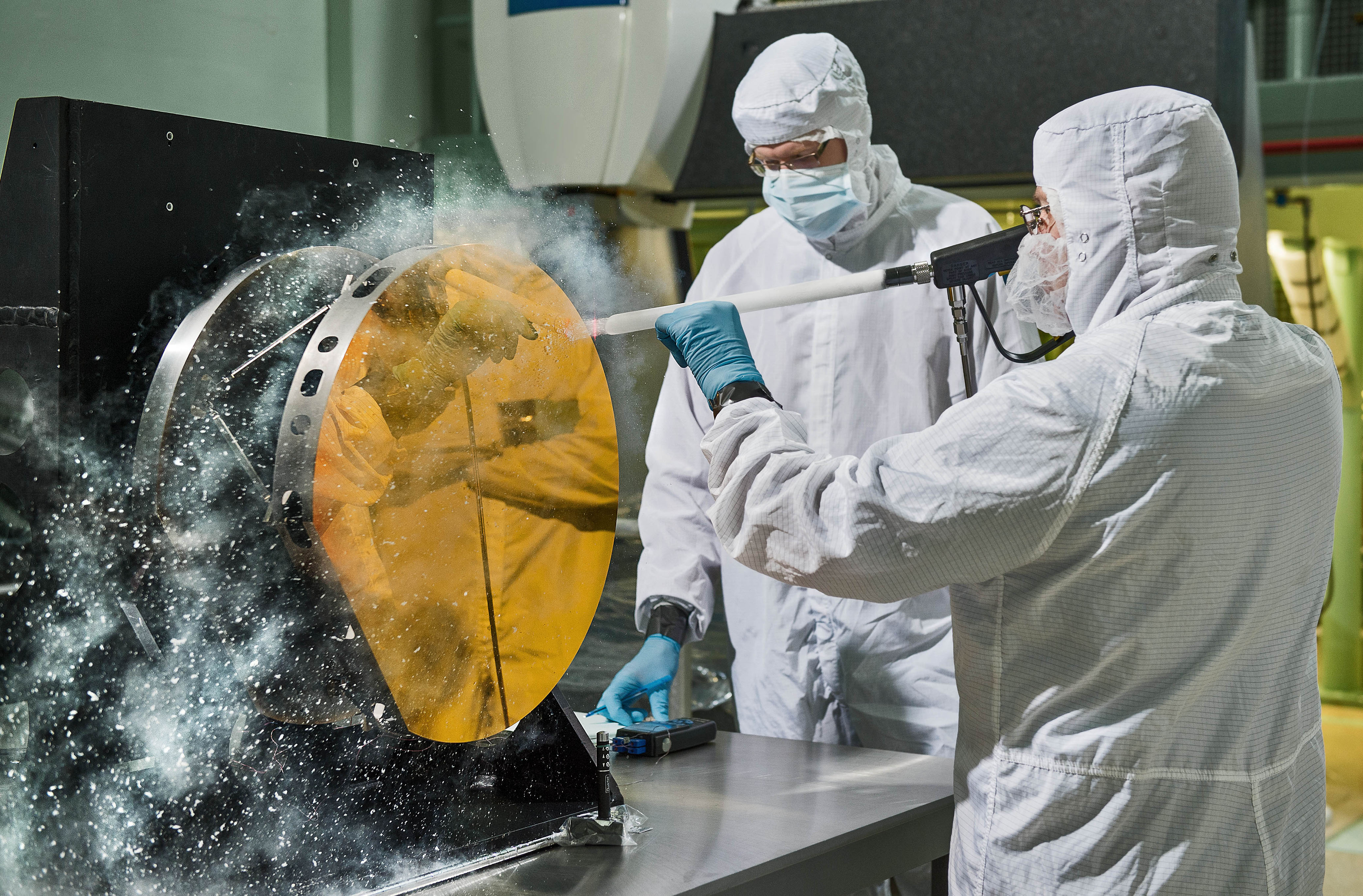 Two Exelis Inc. engineers are practicing  snow cleaning'  on a test telescope mirror for the James Webb Space Telescope at NASA's Goddard Space Flight Center in Greenbelt, Maryland.
