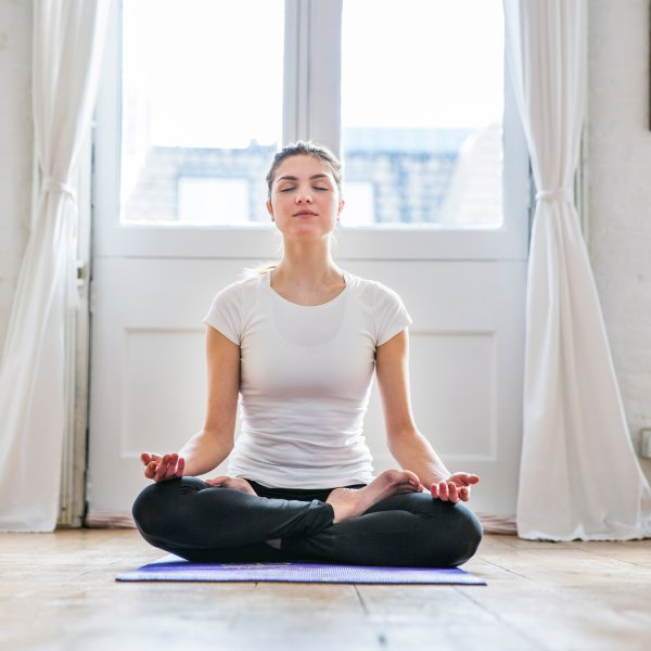 Young woman practicing yoga lotus position in apartment