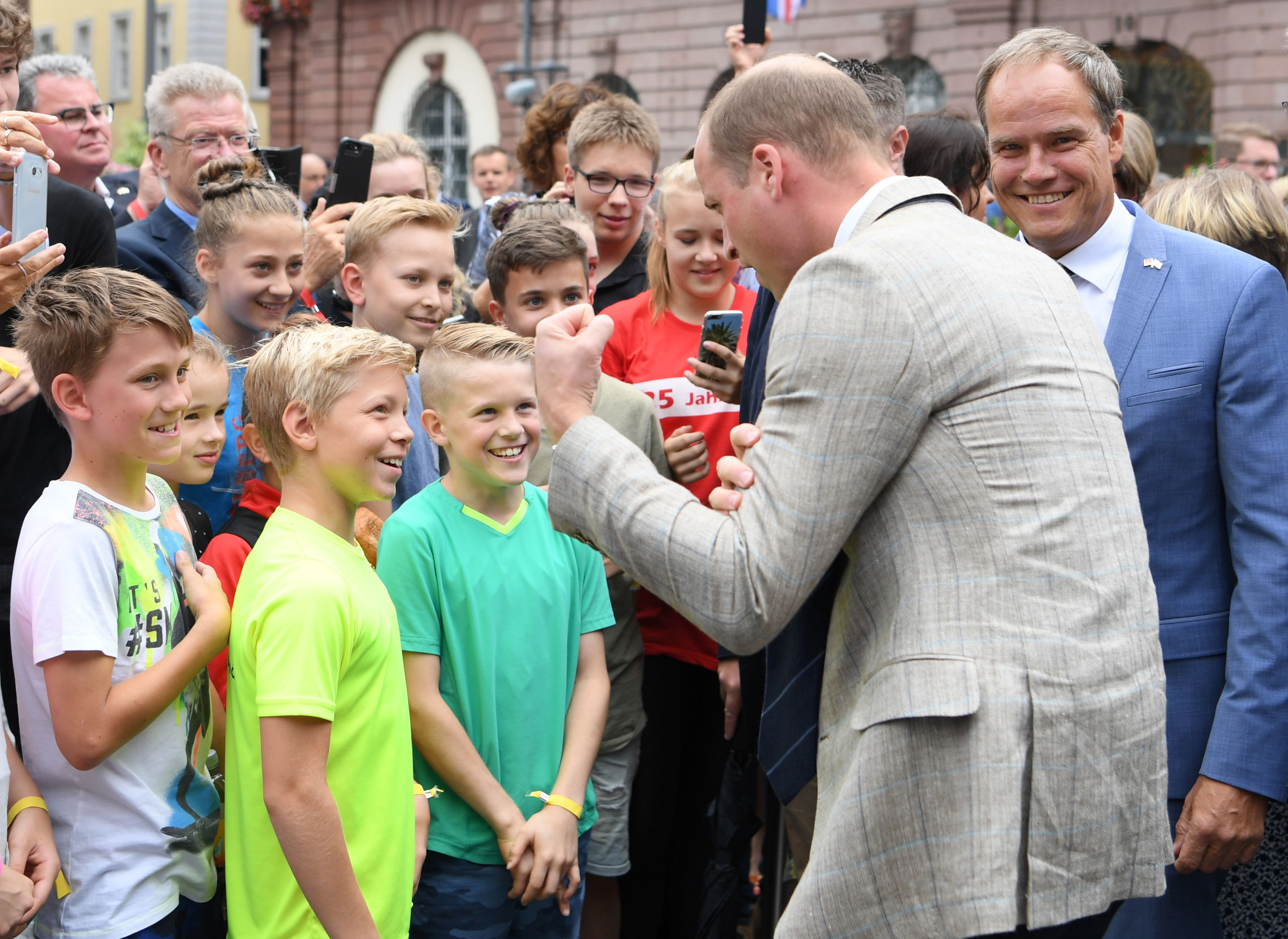 Prince William, Duke of Cambridge, talks to children during a visit to the market in the historic center of southern town of Heidelbergon, Germany, on July 20, 2017.