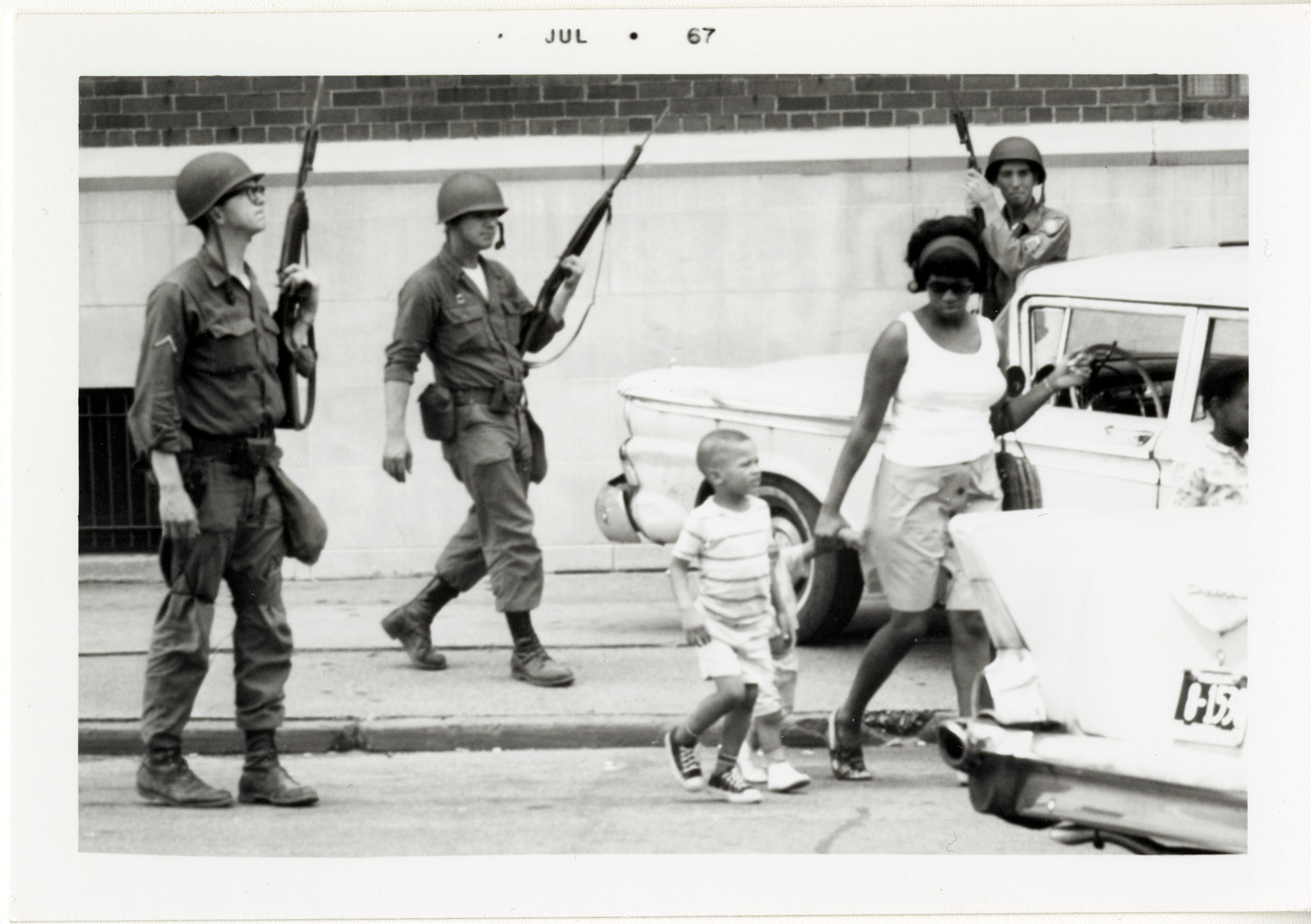 A woman and her children carry on with their daily activities as Michigan National Guardsmen patrol the streets in Detroit.