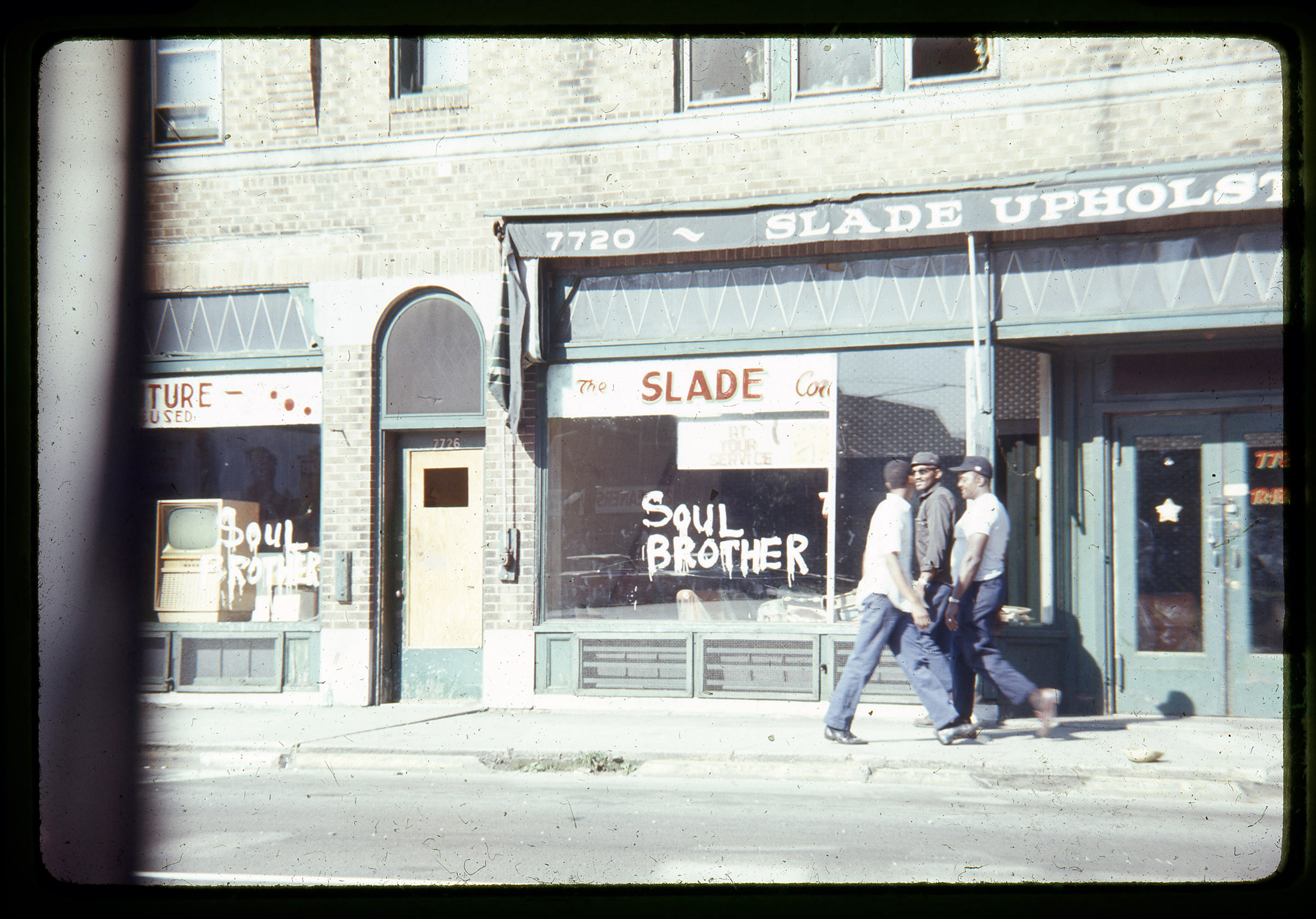 """Citizens walk past a store spray painted with the phrase """"Soul Brother,"""" signifying the store is African American-owned, in an attempt to prevent vandalism and looting."""