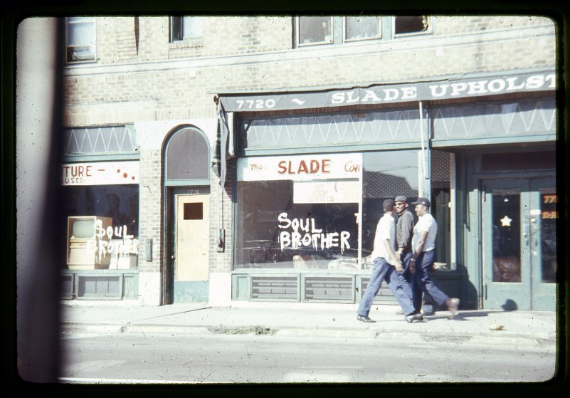 """Citizens walk past a store spray painted with the phrase """"Soul Brother,"""" signifying the store is African American owned in an attempt to prevent vandalism and looting."""