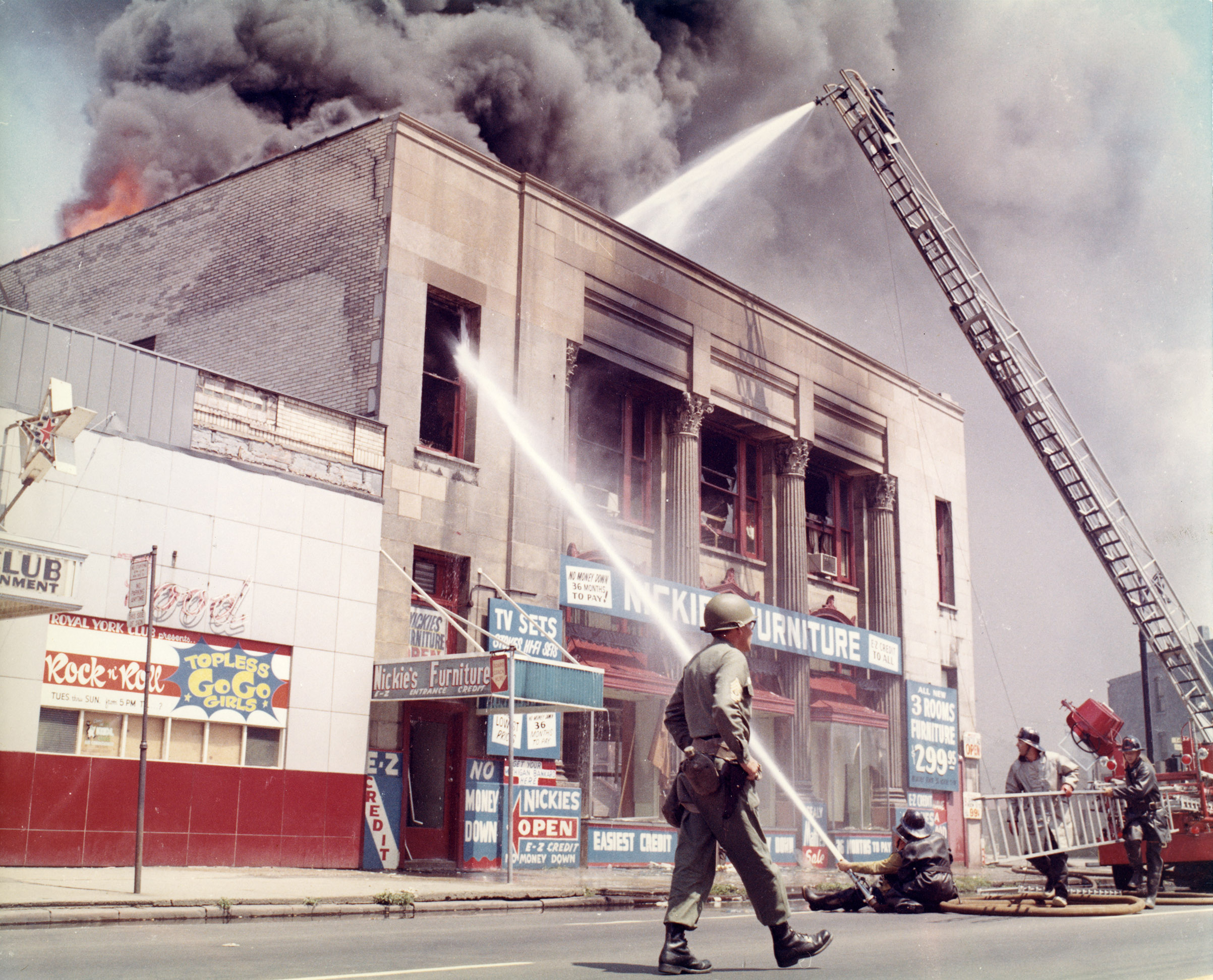 A U.S. Army soldier patrols the streets as Detroit firefighters suppress flames that have broken through the rooftop of a neighborhood furniture store.
