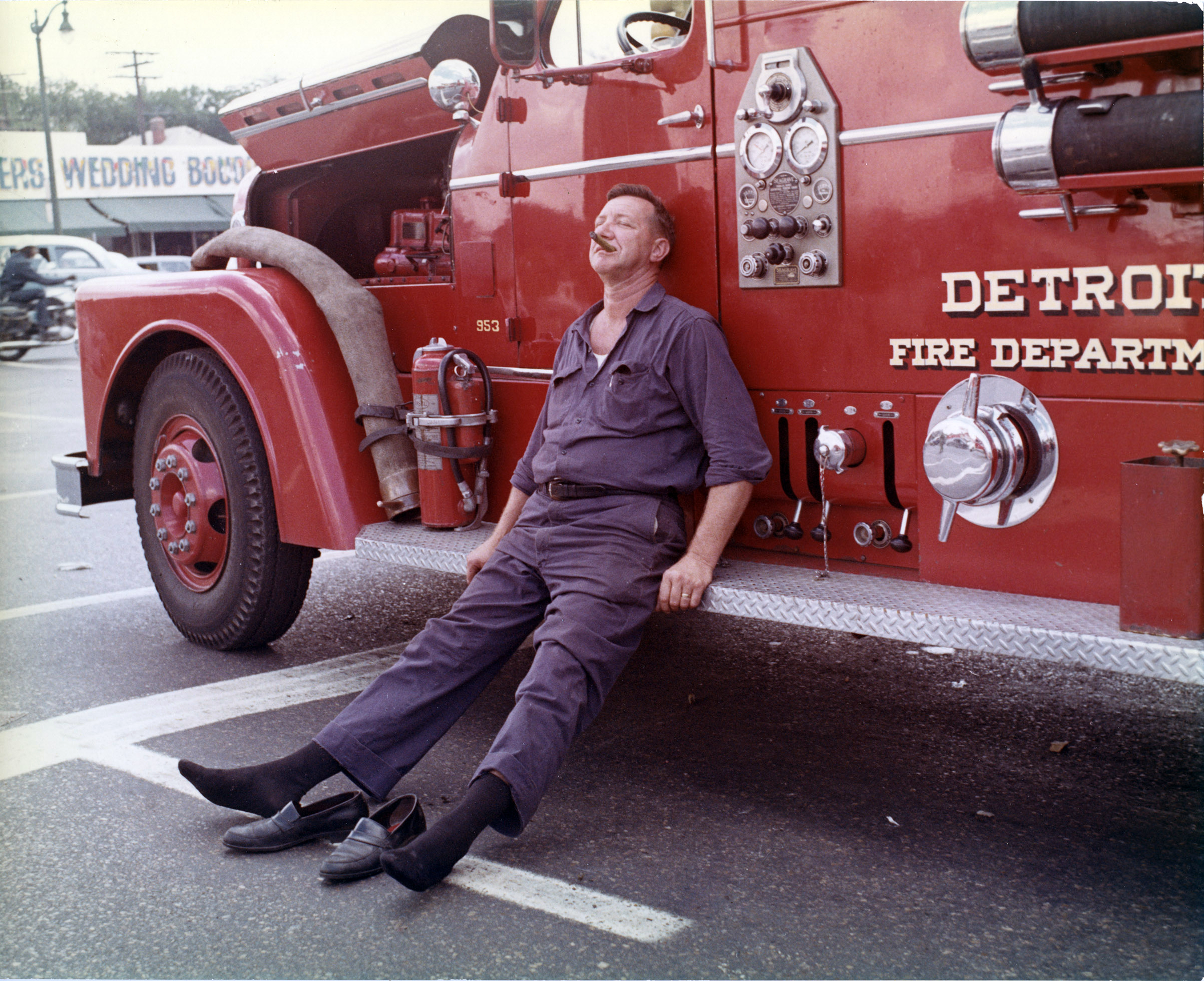A Detroit firefighter collapses against the side of a department vehicle after battling one of the 1,609 structures that were damaged in the city during the July '67 protests.