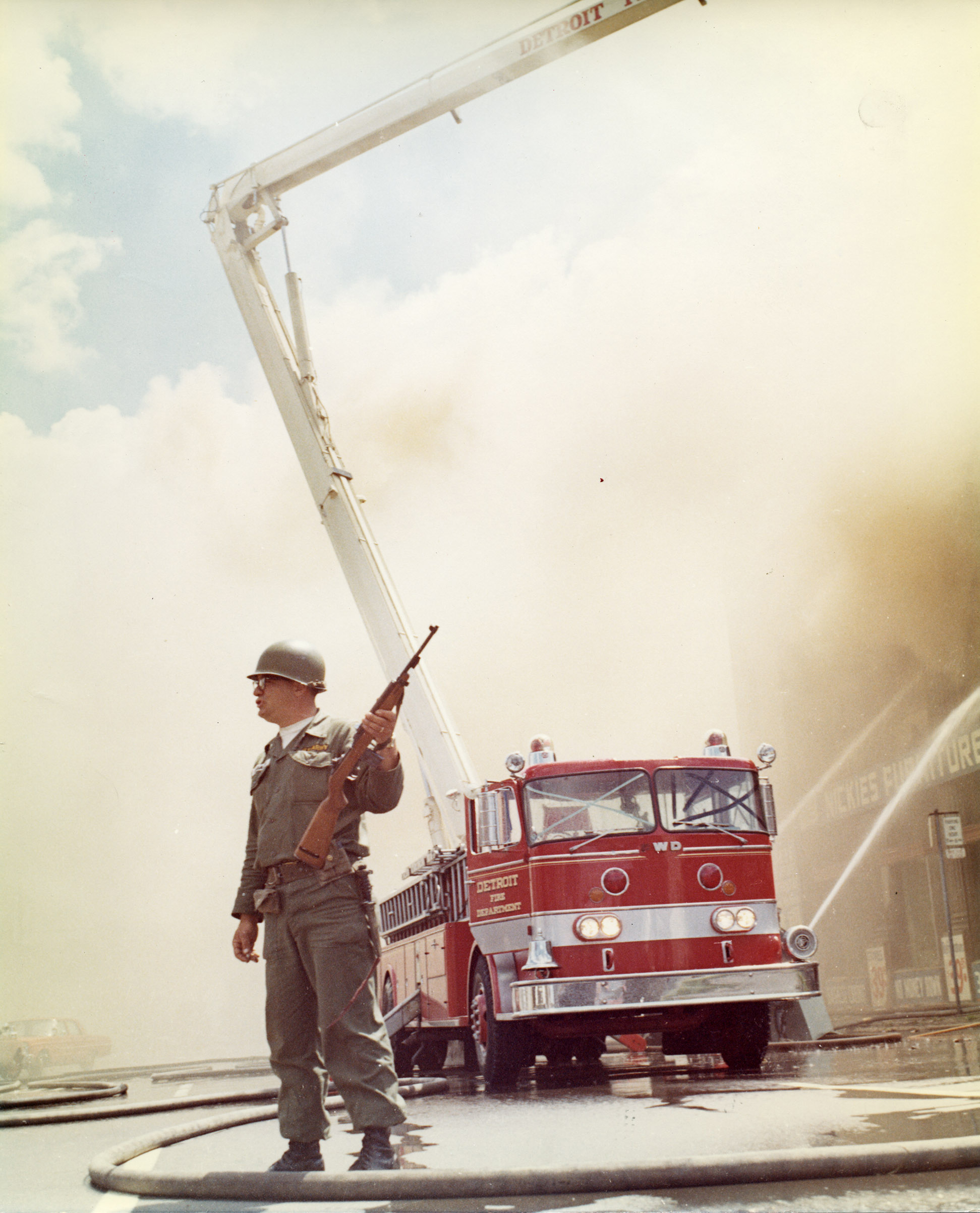A U.S. army soldier watches the streets while the Detroit Fire Department extinguishes a blaze at Nickie's Furniture store on Grand River Avenue near Forest in Detroit.