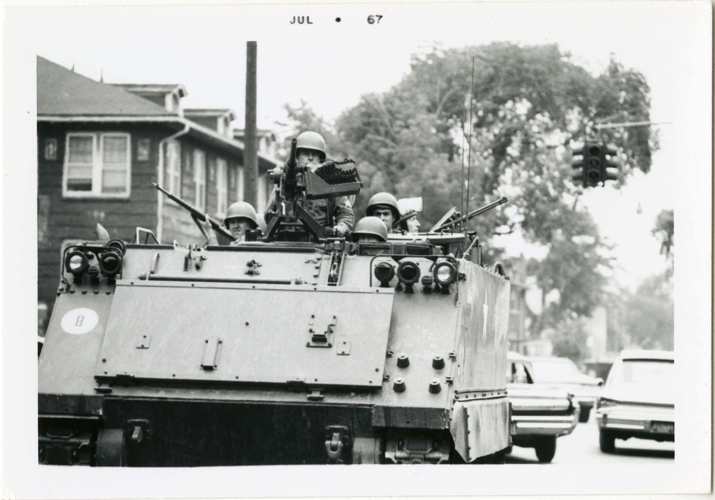 Michigan National Guardsmen patrol the streets of Detroit in an armored personal carrier, also known as a tank.