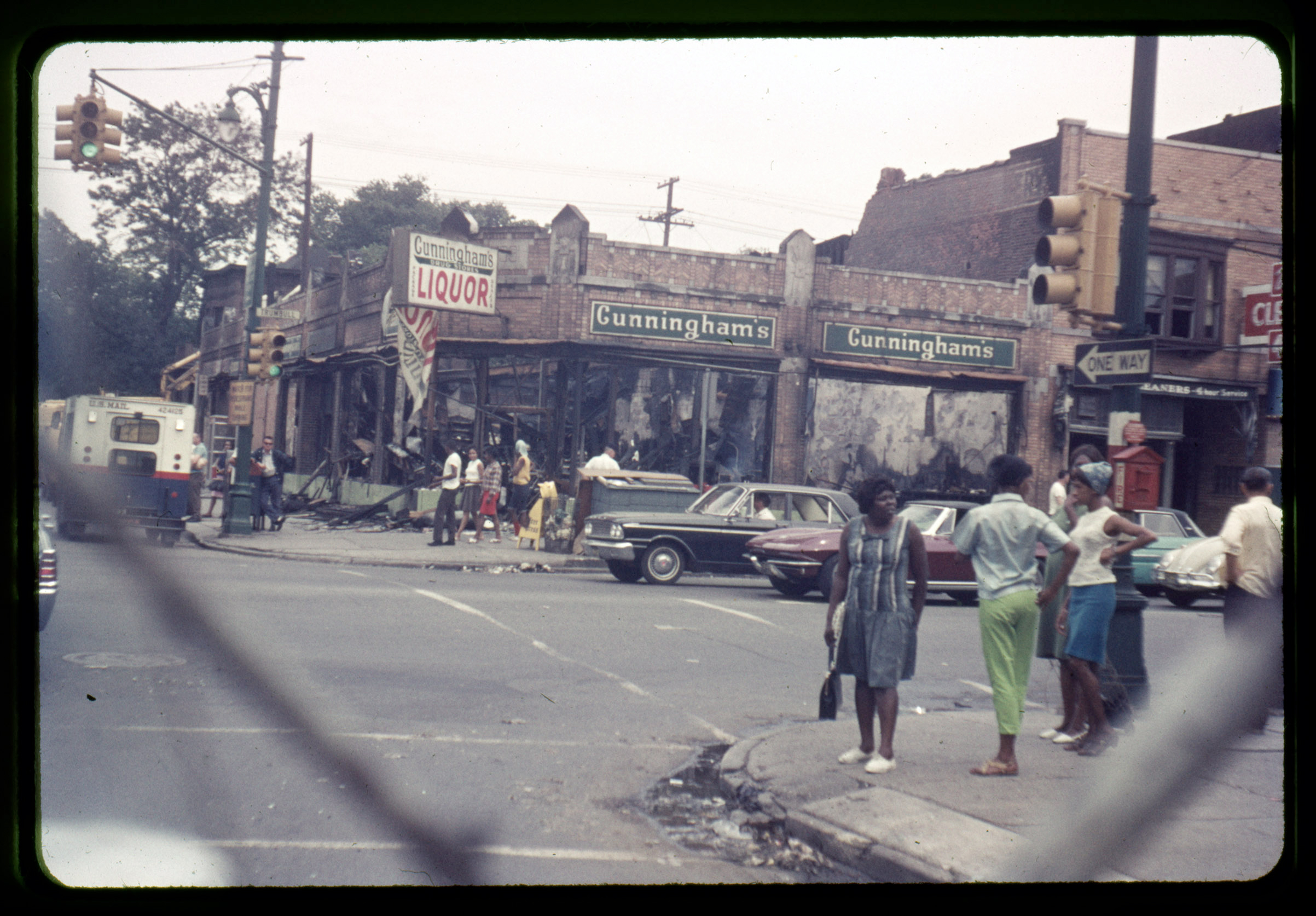 Pedestrians and bystanders observe the devastated buildings on the corner of Trumbull and Forest Avenue in Detroit, July 1967.