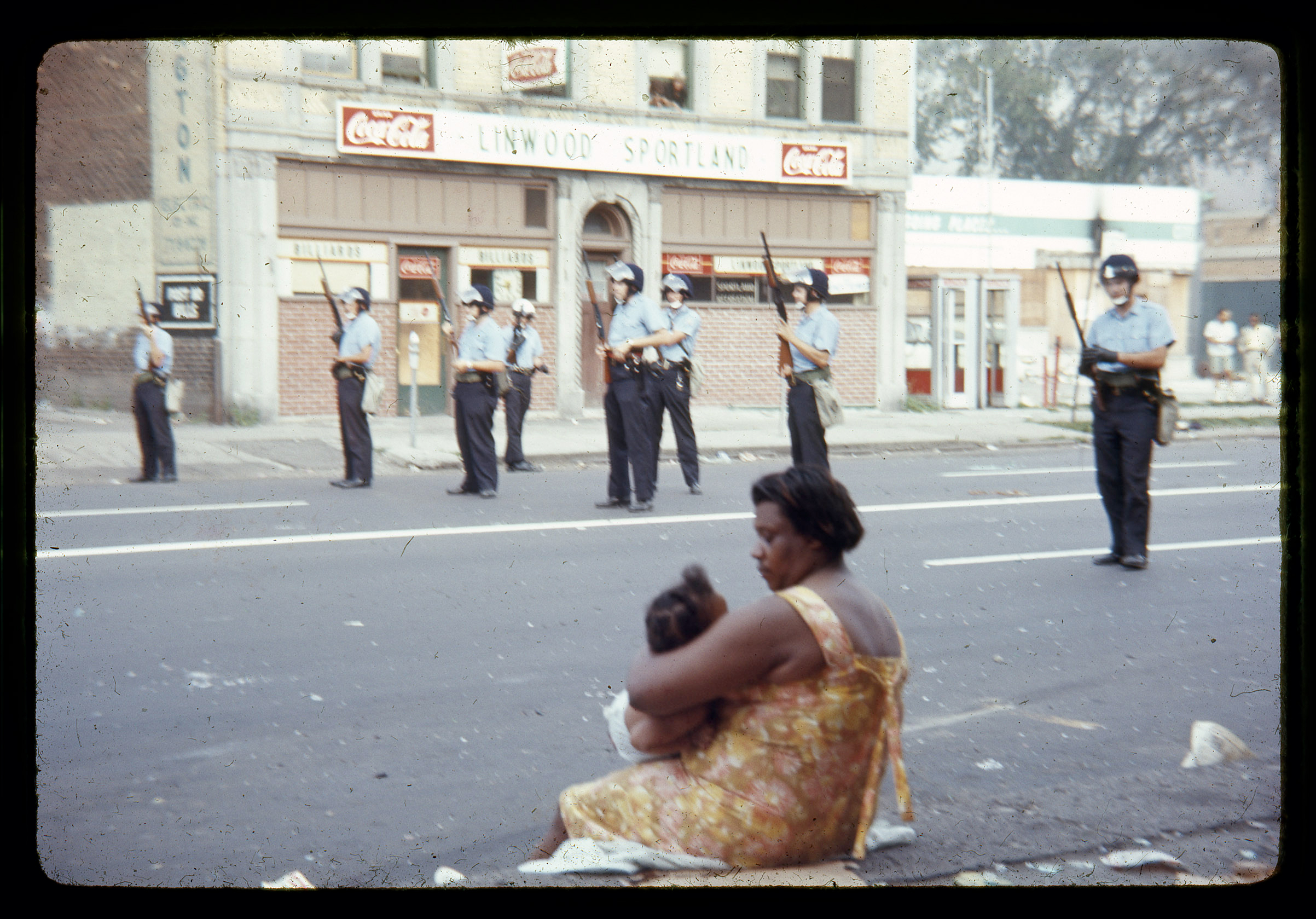 Several Detroit police officers clad in riot gear guard the streets of Detroit as a woman and child look on.